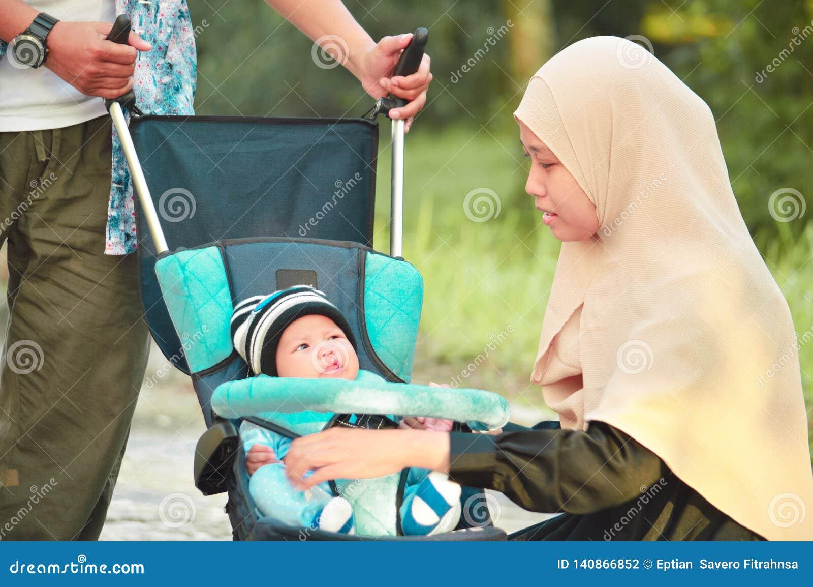 Η ασιατικοί μουσουλμανικοί μητέρα και ο πατέρας hijabi περπατούν μέσω του πάρκου με το γιο στον περιπατητή
