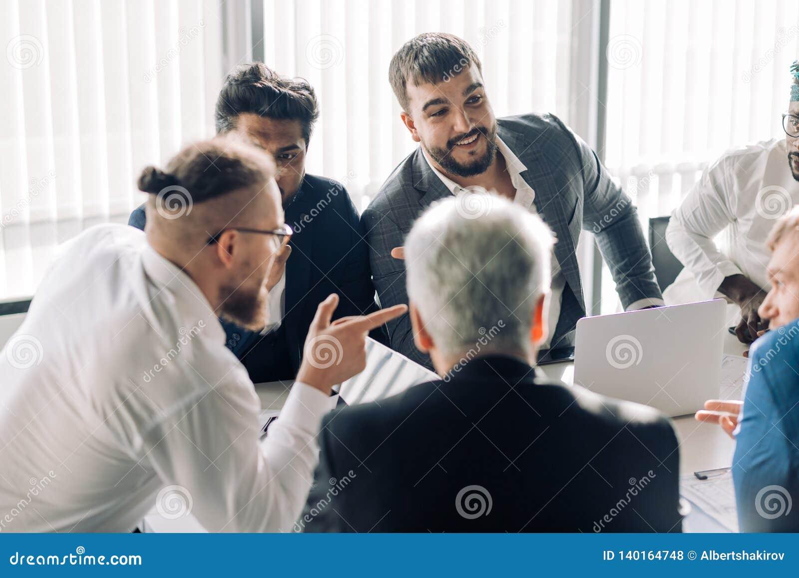 Η εταιρική διαφυλετική επιχειρησιακή ομάδα με τον εύθυμο ηγέτη σε μια συνεδρίαση, κλείνει επάνω