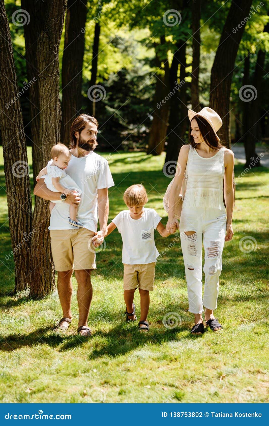 Η όμορφη γυναίκα φορά τα άσπρους ενδύματα και τους περιπάτους καπέλων με τον όμορφους πατέρα και τα παιδιά στο θαυμάσιο πάρκο στο