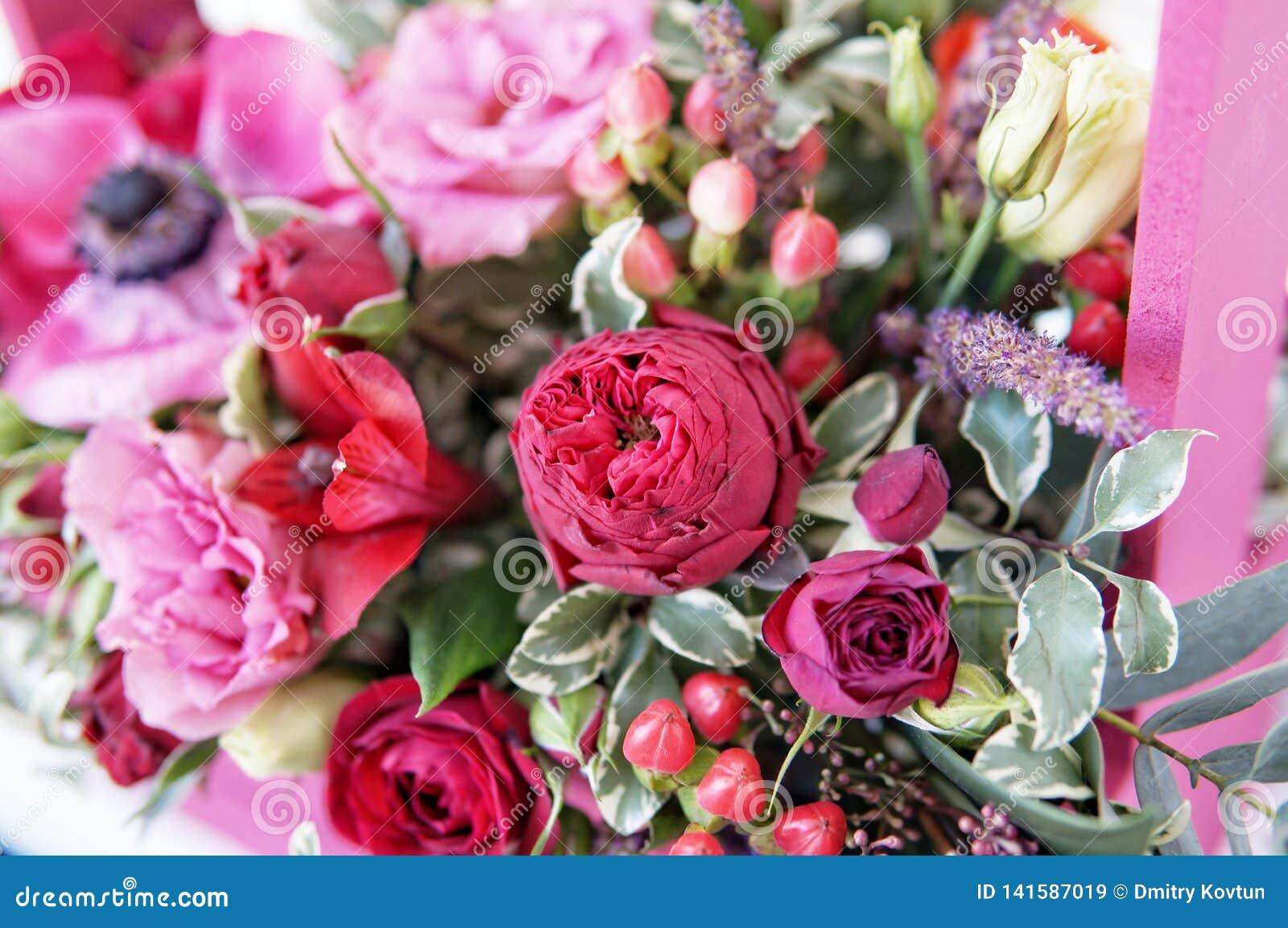 Η όμορφη floral ρύθμιση του κοκκίνου, του ροζ και burgundy ανθίζει σε ένα ρόδινο ξύλινο κιβώτιο