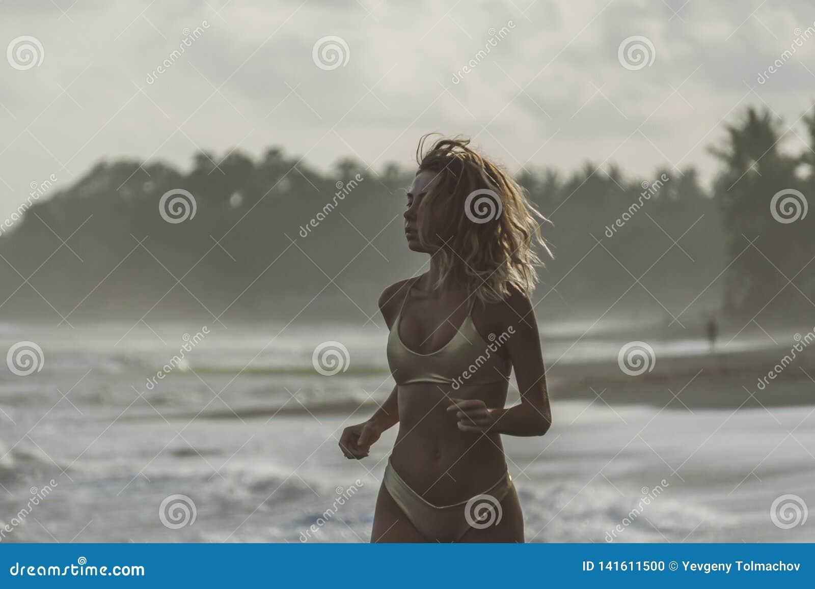 Η πανέμορφη νέα γυναίκα στο χρυσό μπικίνι με τον αθλητισμό λογαριάζει τα τρεξίματα το βράδυ στην παραλία