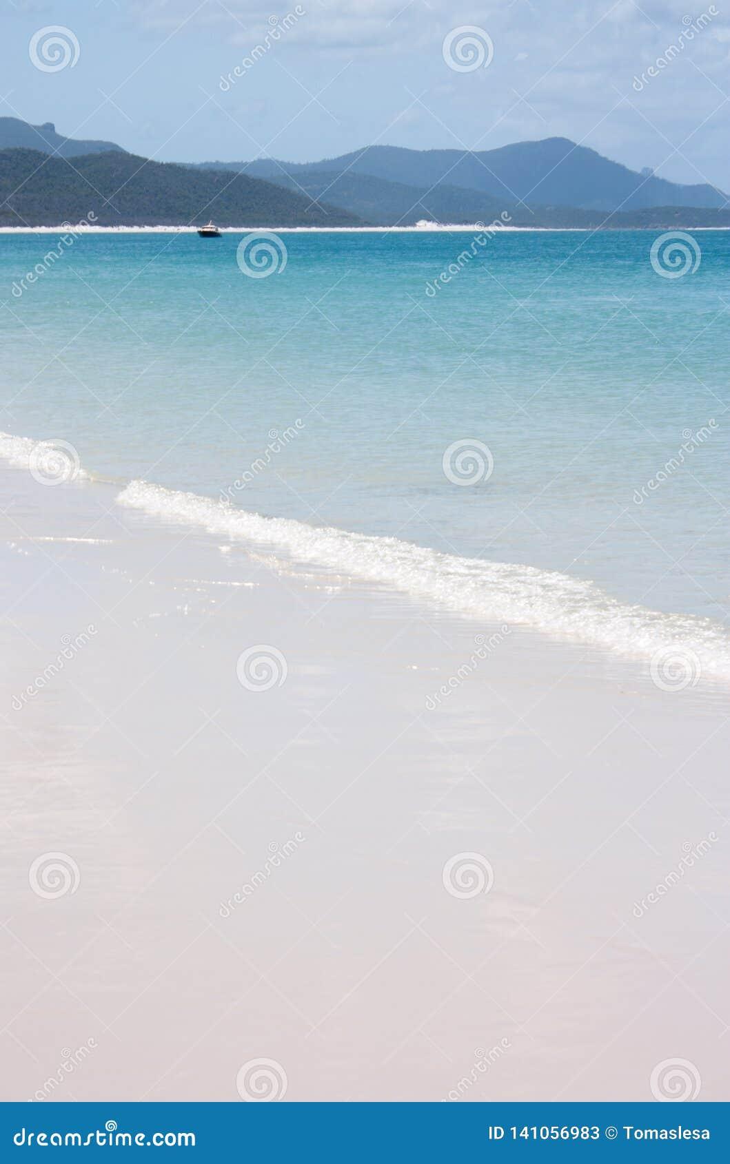 Η παραλία Whitehaven στο Whitsundays στην Αυστραλία με μια μικρή βάρκα στην απόσταση