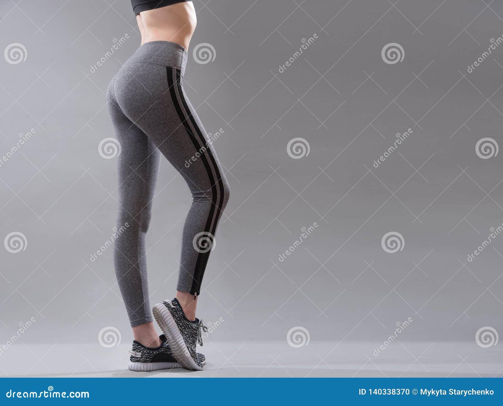 Θηλυκά sportswear ενδύματα στο τέλειο σώμα, τα πάνινα παπούτσια και τα γκρίζα εσώρουχα περικνημίδων