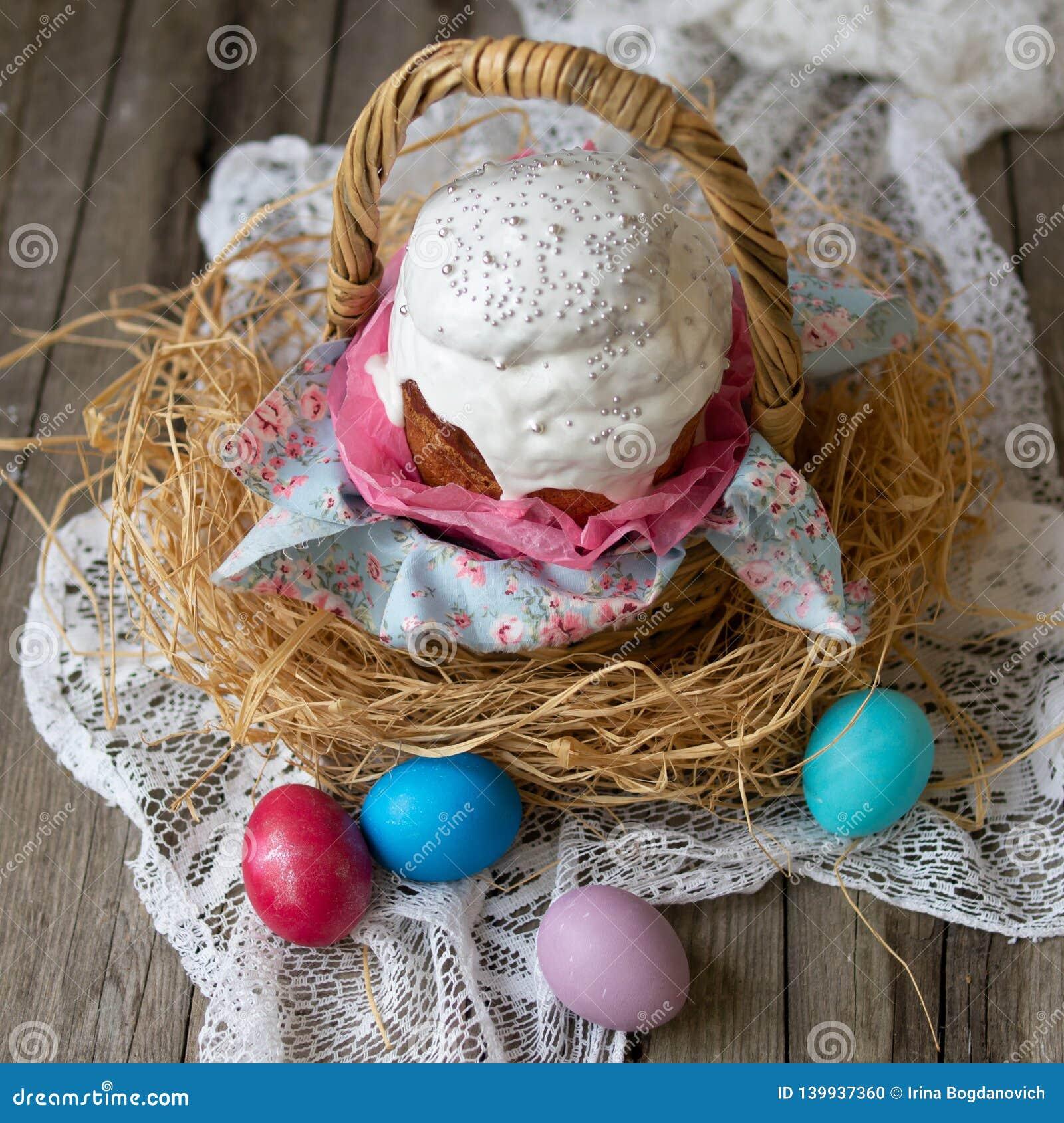 Κέικ Πάσχας - kulich Το παραδοσιακό γλυκό ψωμί Πάσχας διακόσμησε την άσπρη τήξη στο καλάθι αχύρου και χρωμάτισε τα αυγά στην πετσ