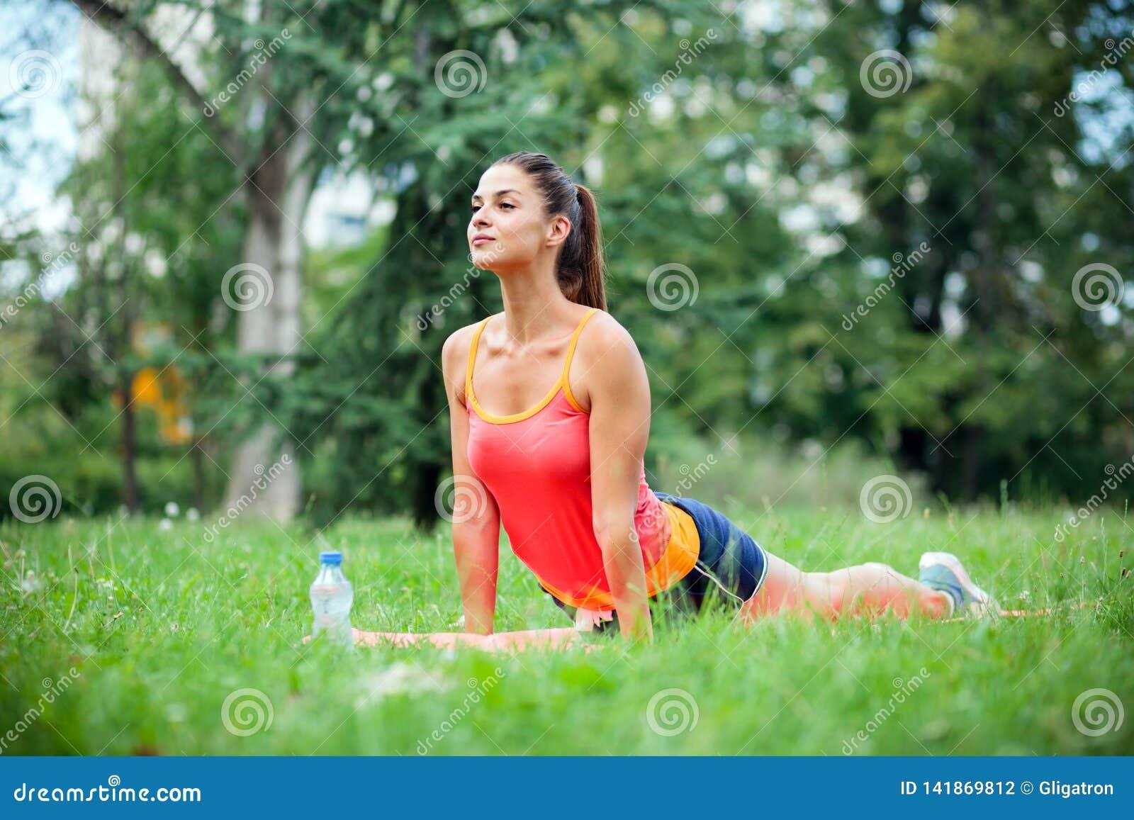 Καθορισμένη κατάλληλη νέα γυναίκα που κάνει τις θιβετιανές ασκήσεις γιόγκας ιεροτελεστιών στο πάρκο
