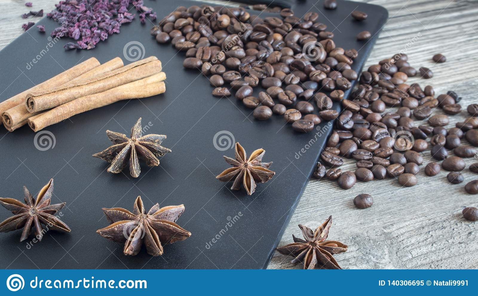 Καρυκεύματα και τρόφιμα στο ξύλινο υπόβαθρο Ραβδιά κανέλας, γλυκάνισο αστεριών και φασόλια καφέ Συστατικά για το εγχώριο μαγείρεμ