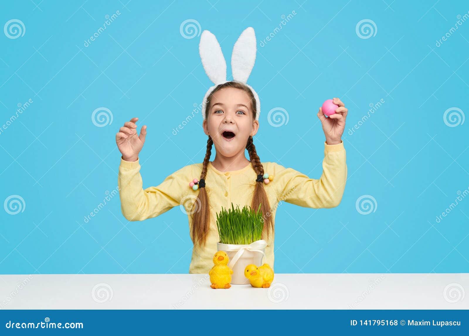 Κατάπληκτο κορίτσι στα αυτιά λαγουδάκι που γιορτάζει Πάσχα