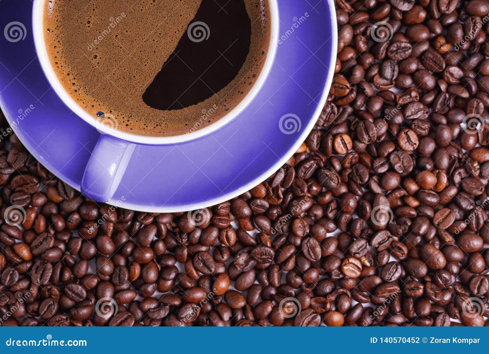 Καφές στο πορφυρό φλυτζάνι στον πίνακα που περιβάλλεται με τα φασόλια καφέ