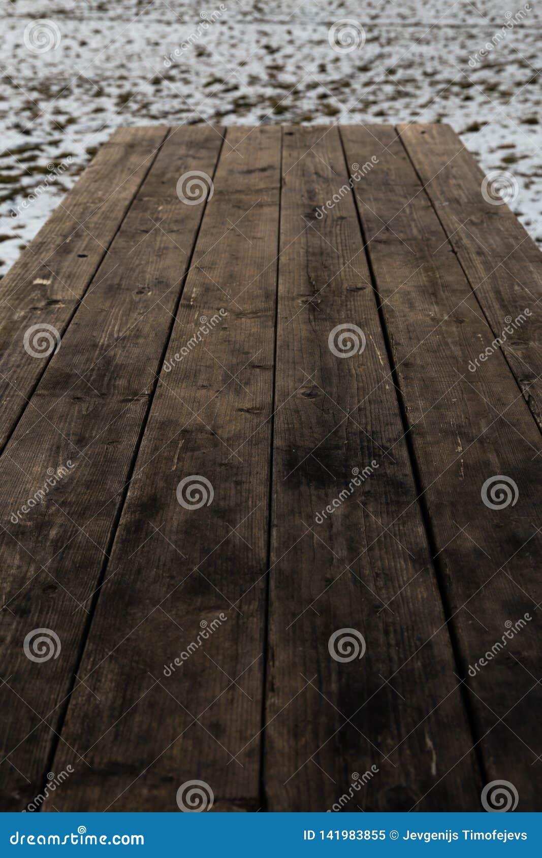 Κενός ξύλινος πίνακας με το χιόνι bokeh για έναν τομέα εστιάσεως ή μια σύσταση πικ-νίκ τροφίμων