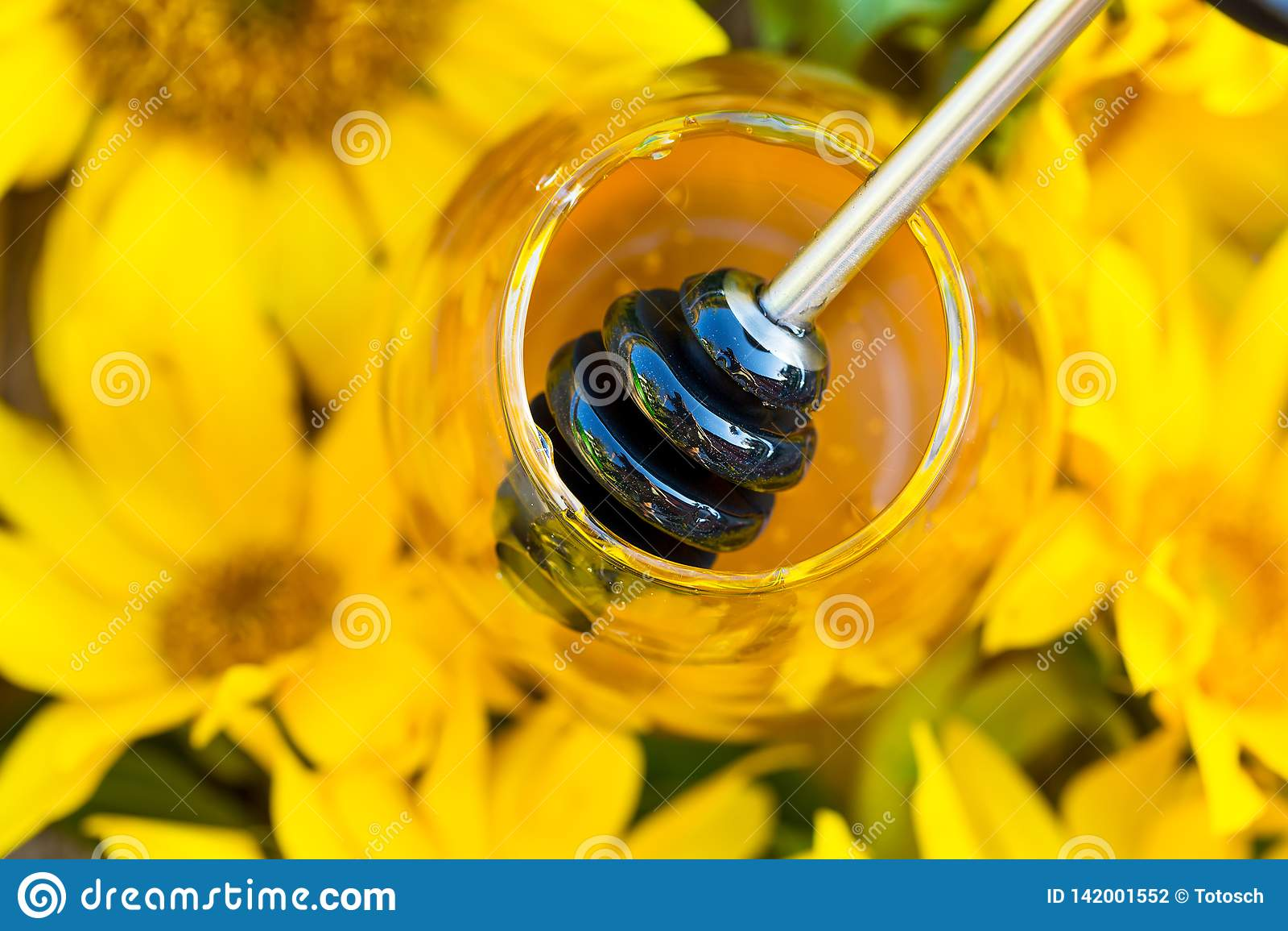 Κινηματογράφηση σε πρώτο πλάνο του συνόλου βάζων με το μέλι και το μέλι-κουτάλι στη μέση των ηλίανθων