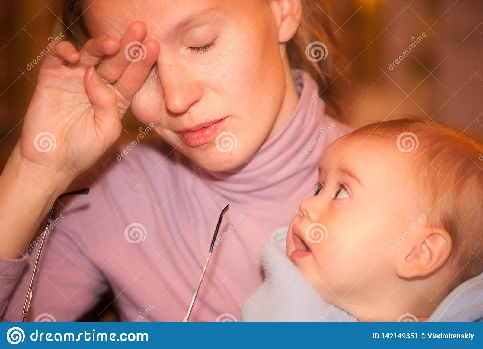 Κουρασμένος mom με ένα περίεργο μωρό στα όπλα της