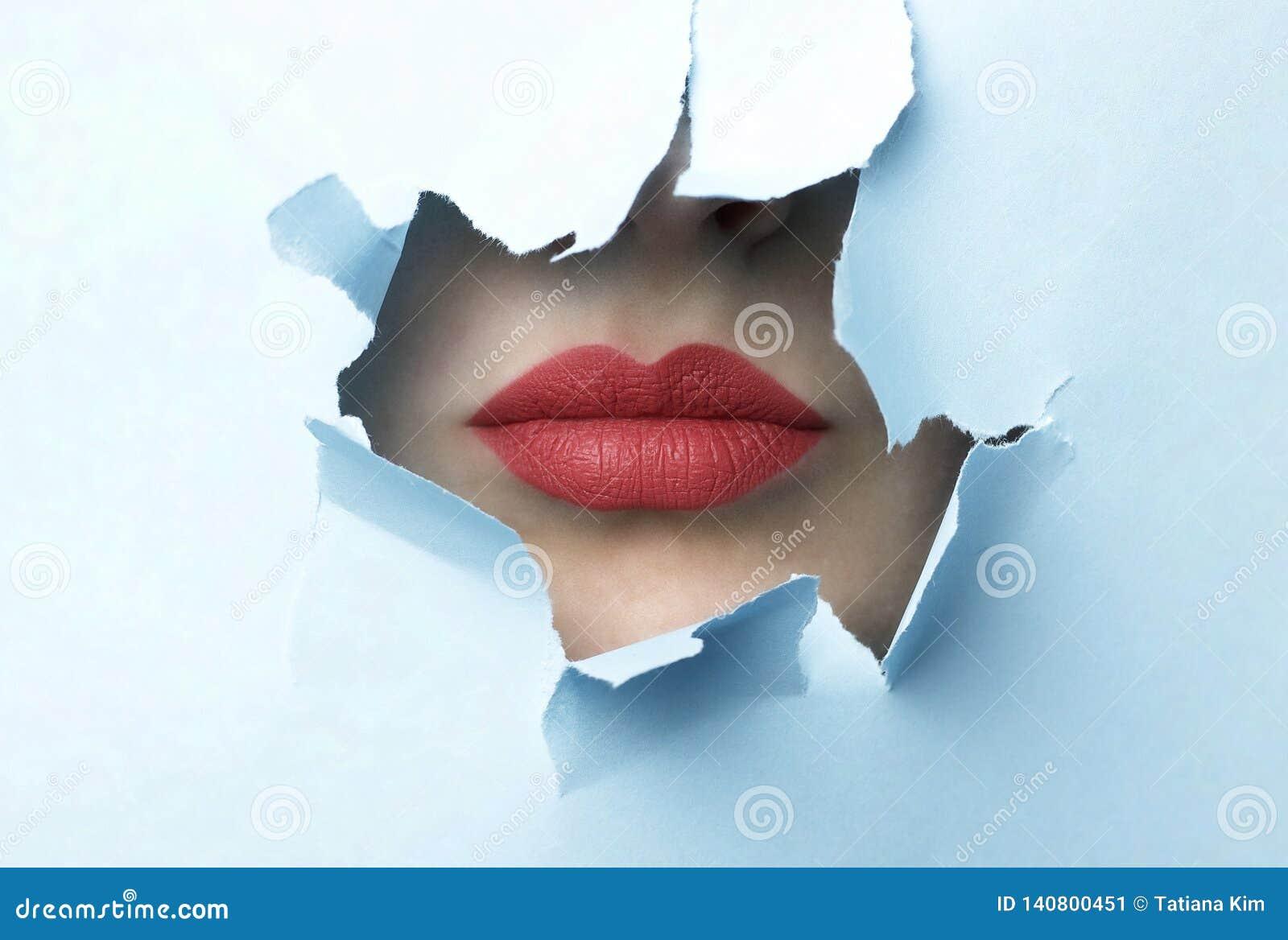 Κόκκινα χείλια και μπλε σχισμένο υπόβαθρο εγγράφου