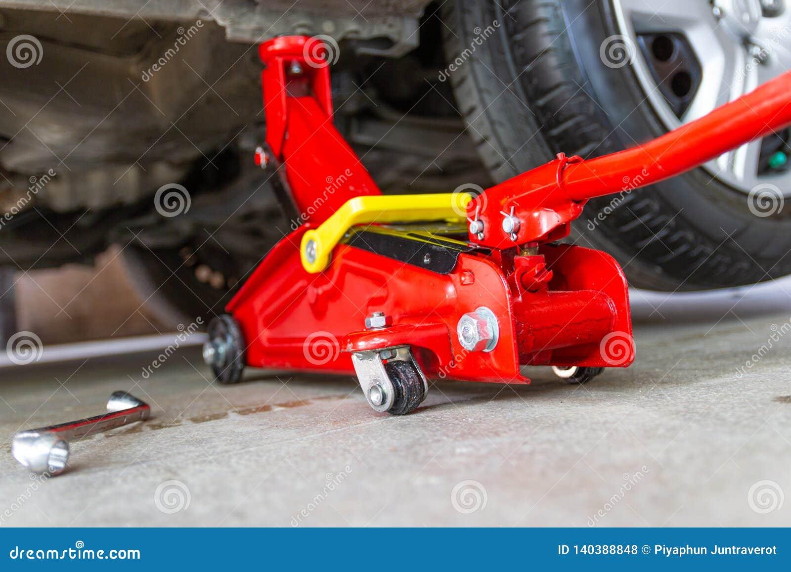 Κόκκινο αυτοκίνητο ανελκυστήρων γρύλων εργαλείων για τον έλεγχο επισκευής