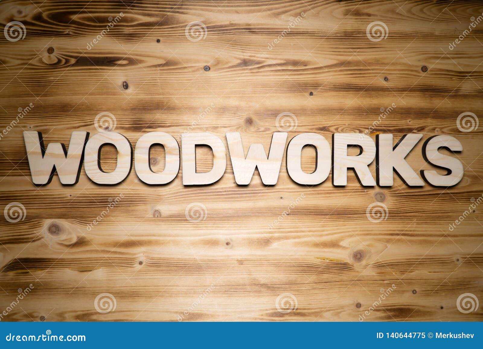 Λέξη Woodworks φιαγμένη από ξύλινα κεφαλαία γράμματα στον ξύλινο πίνακα