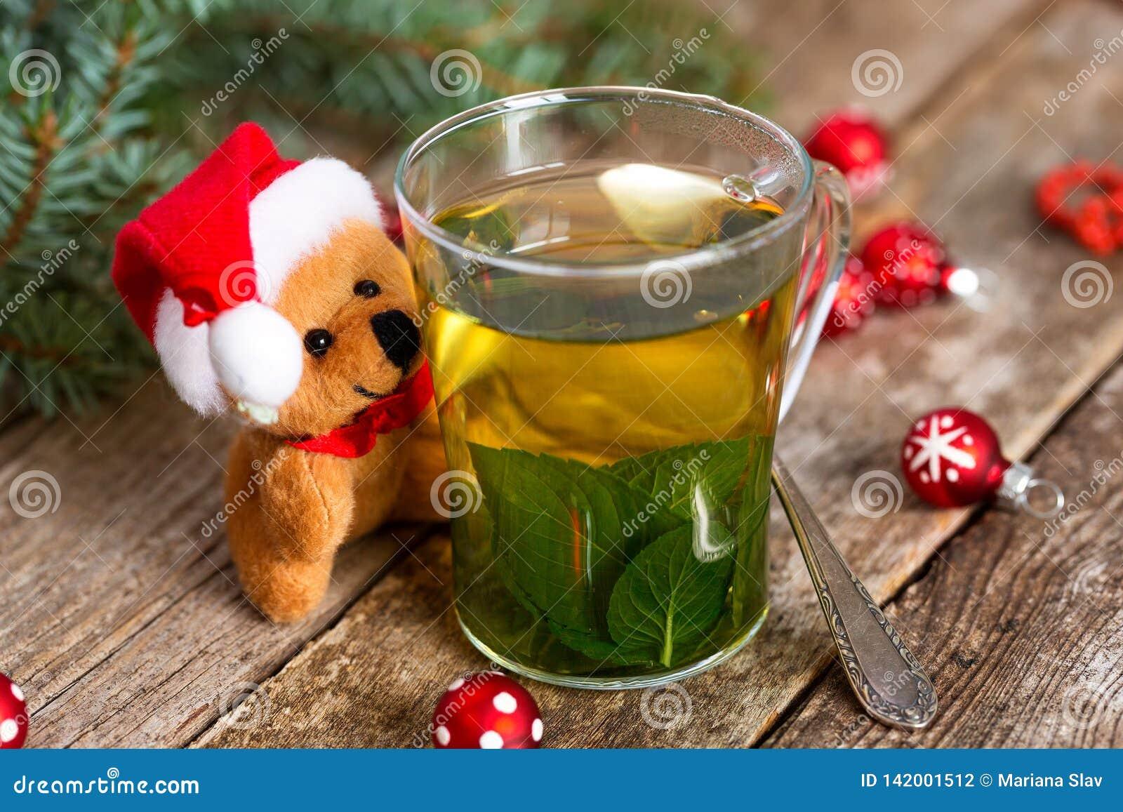 Λίγο Santa αντέχει ένα φλυτζάνι του καυτού τσαγιού μεντών