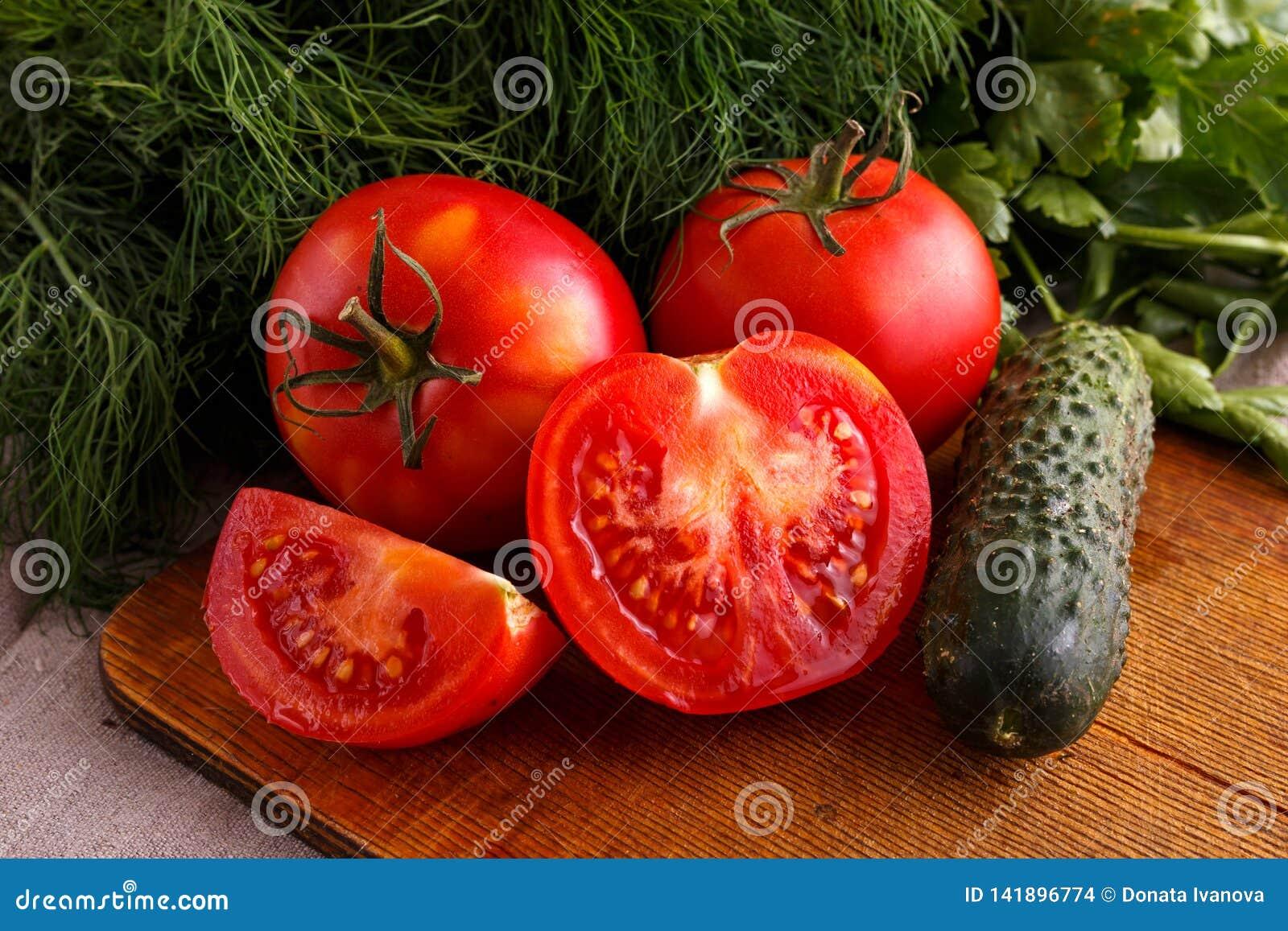 Λαχανικά, ώριμες, κόκκινες ντομάτες και πράσινα αγγούρια