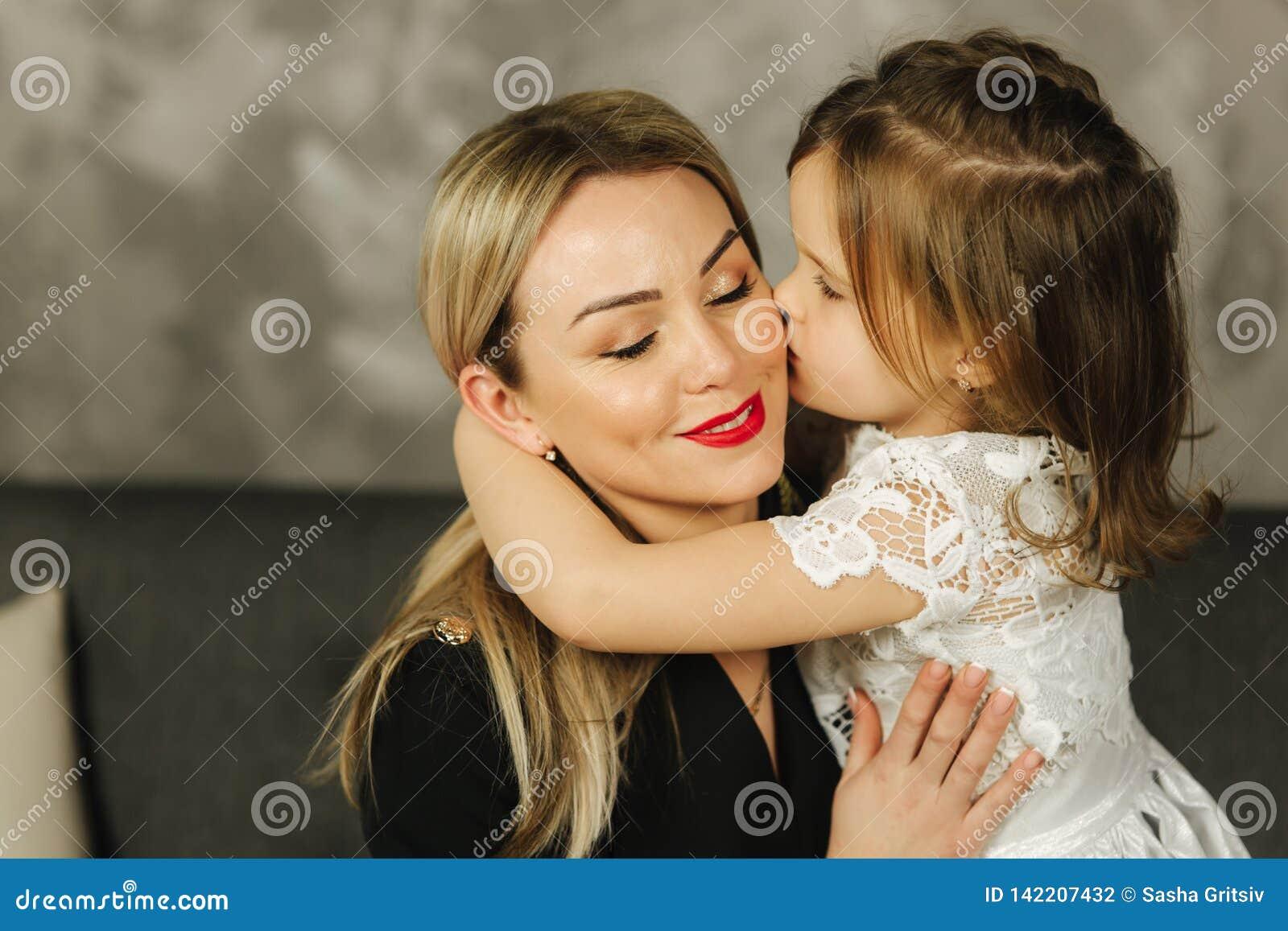 Μητέρα και χαμόγελο αγκαλιάσματος μικρών κοριτσιών Ευτυχές νέο mom με την κόρη της στο σπίτι