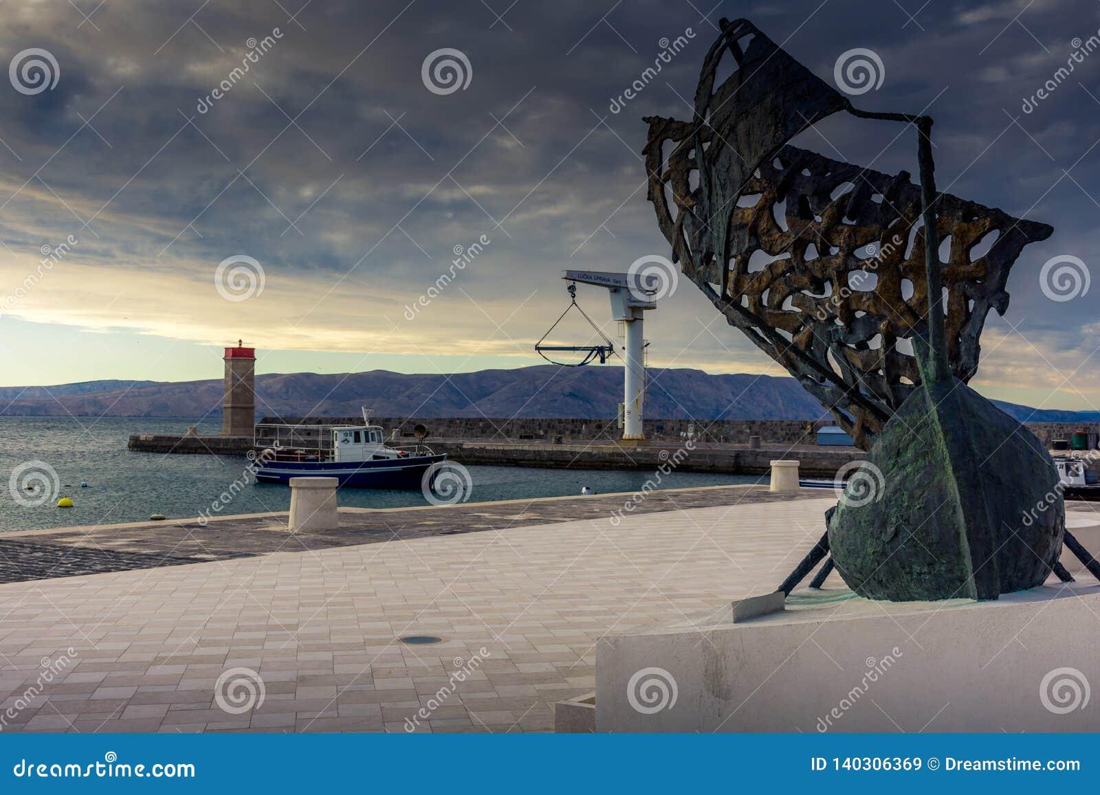 Μια βάρκα σε έναν λιμένα με ένα άγαλμα μιας πλέοντας βάρκας στο πρώτο πλάνο