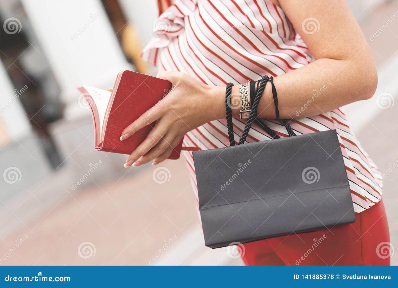 Μια γυναίκα στέκεται με μια μαύρη τσάντα εγγράφου στα χέρια και το μικρό σημειωματάριό της ψωνίζοντας λευκή γυναίκα ποδιών έννοια