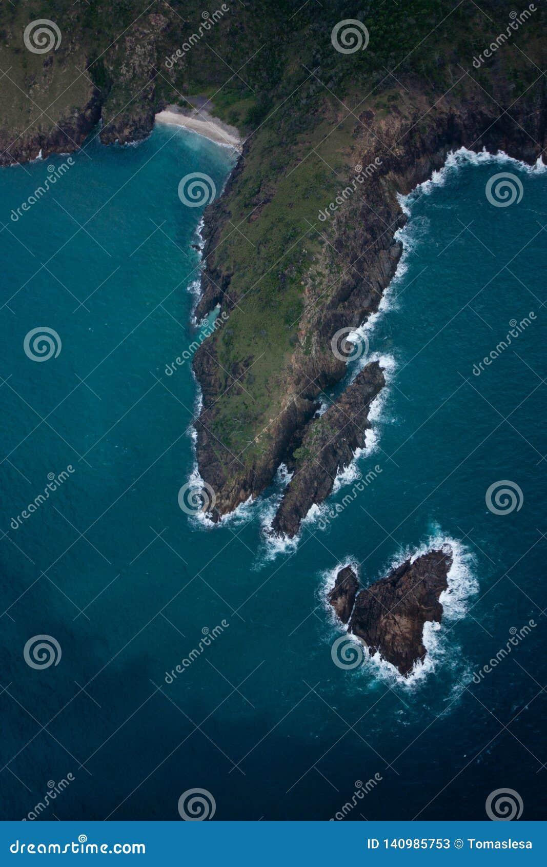 Μια εναέρια άποψη σε ένα νησί και ένα μικρό καρδιά-διαμορφωμένο νησί βράχου σε Whitsundays στην Αυστραλία