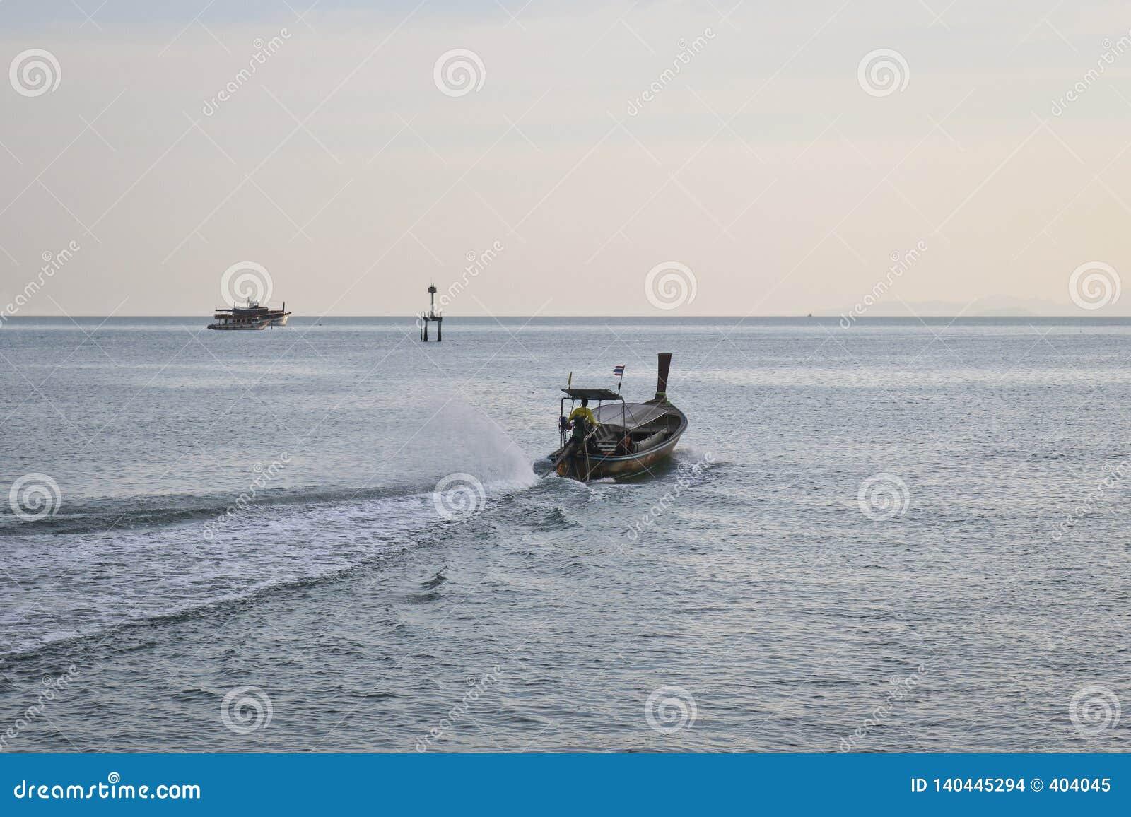 Μια κενή με μακριά ουρά βάρκα μηχανών επιπλέει στη θάλασσα το βράδυ - τέλος της εργάσιμης ημέρας