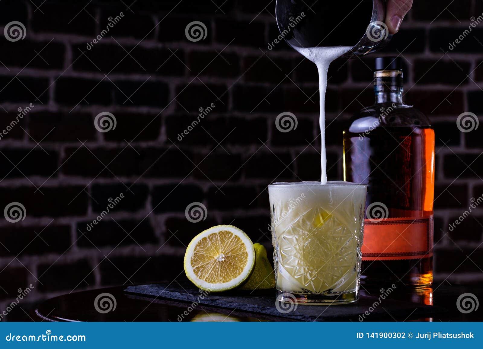 Μια κλασική συνταγή για το ουίσκυ ξινό - το μπέρμπον, το σιρόπι καλάμων και το χυμό λεμονιών, που διακοσμούνται με με το πορτοκάλ