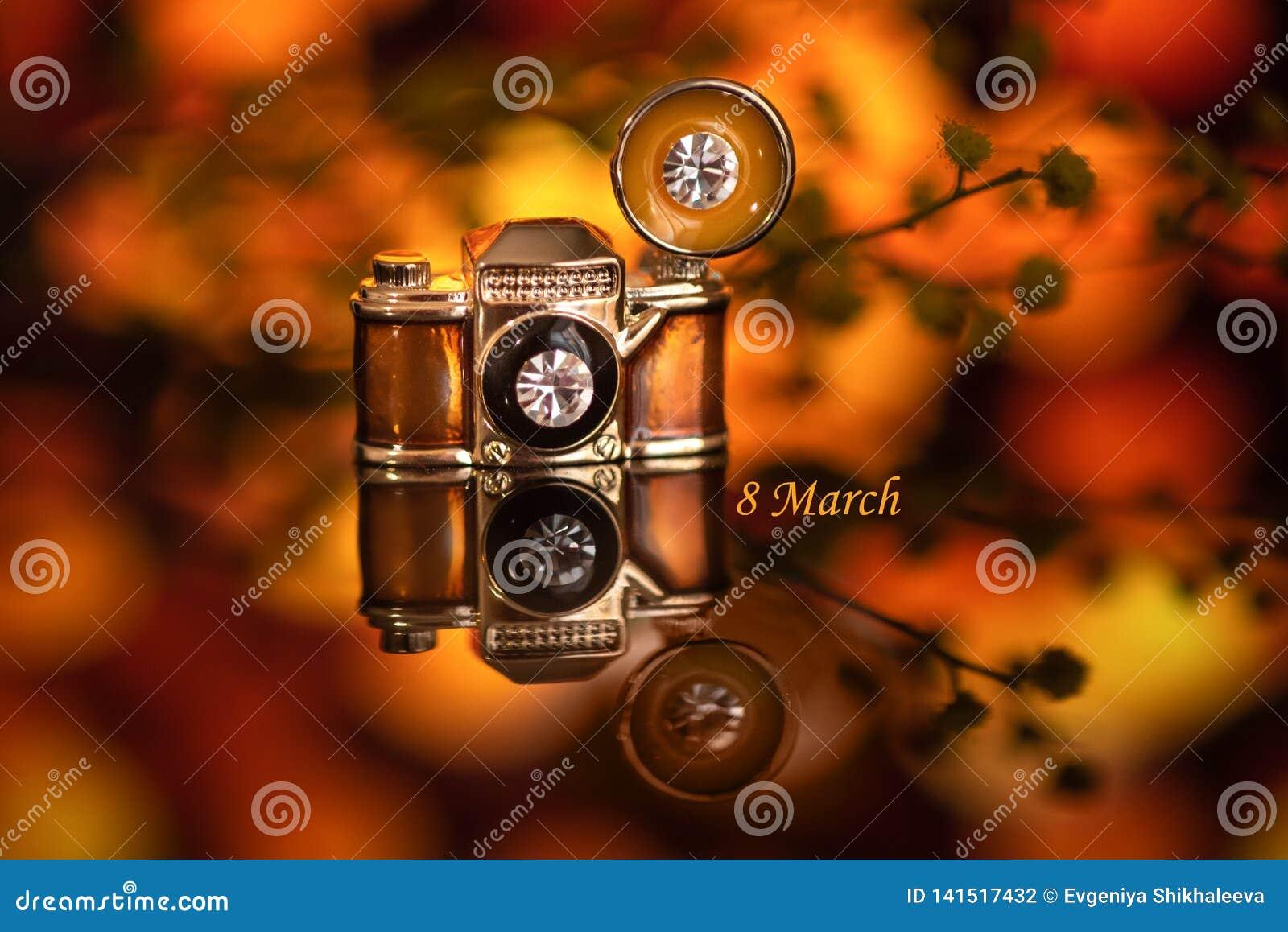 Μια μικρή πόρπη υπό μορφή κάμερας σε ένα πορτοκαλί υπόβαθρο