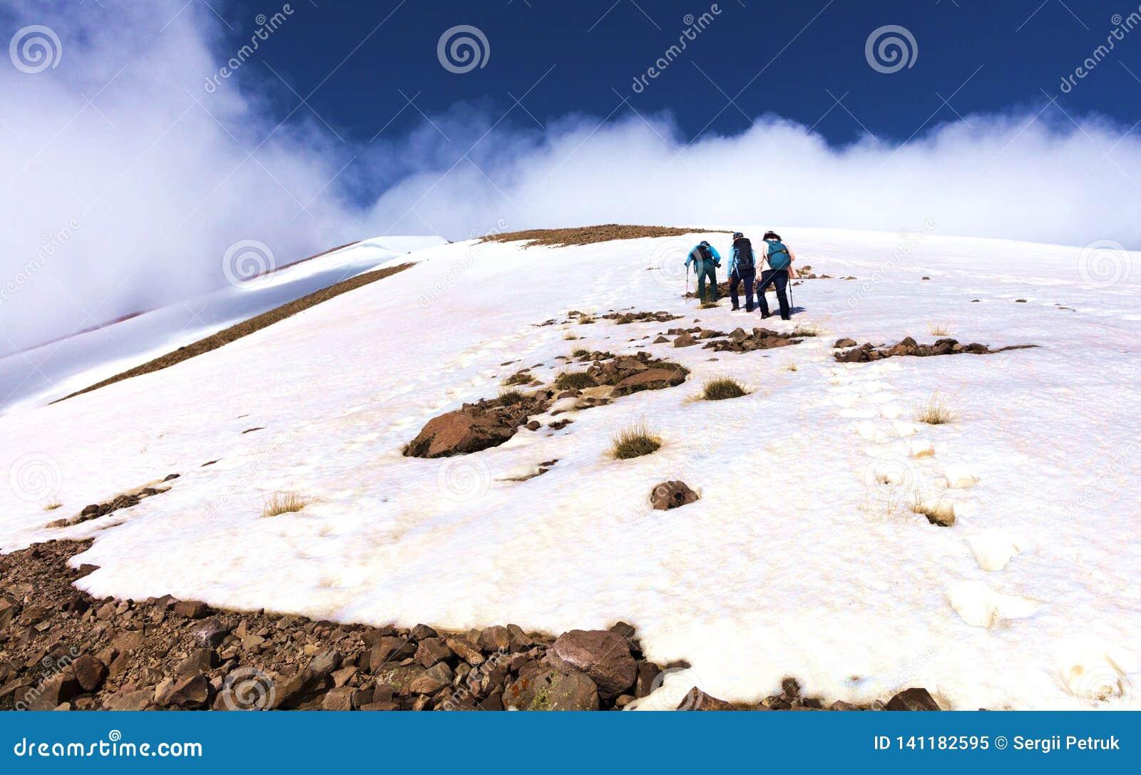 Μια ομάδα τουριστών αναρριχείται δύσκολο χιονισμένο mountainside στην ομιχλώδη σύνοδο κορυφής της