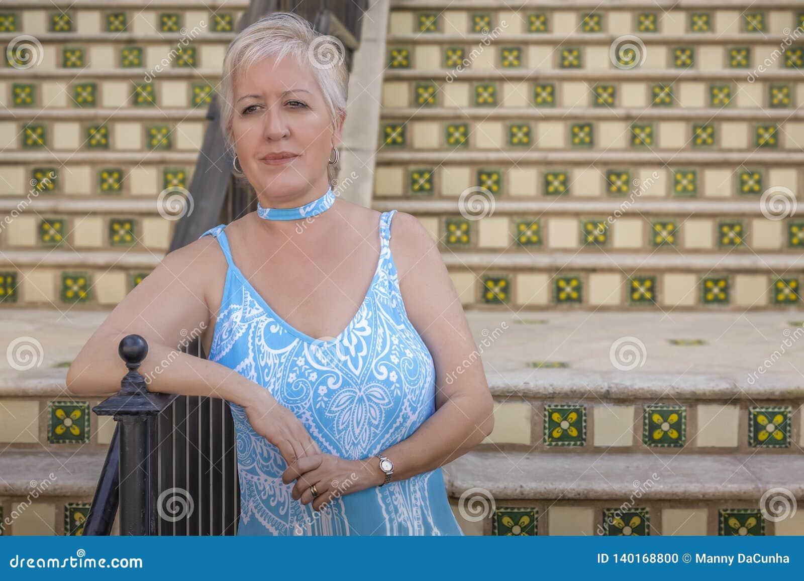 Μια ώριμη σύγχρονη ξανθή γυναίκα περιμένει στο κατώτατο σημείο των βημάτων που κλίνουν στη ράγα
