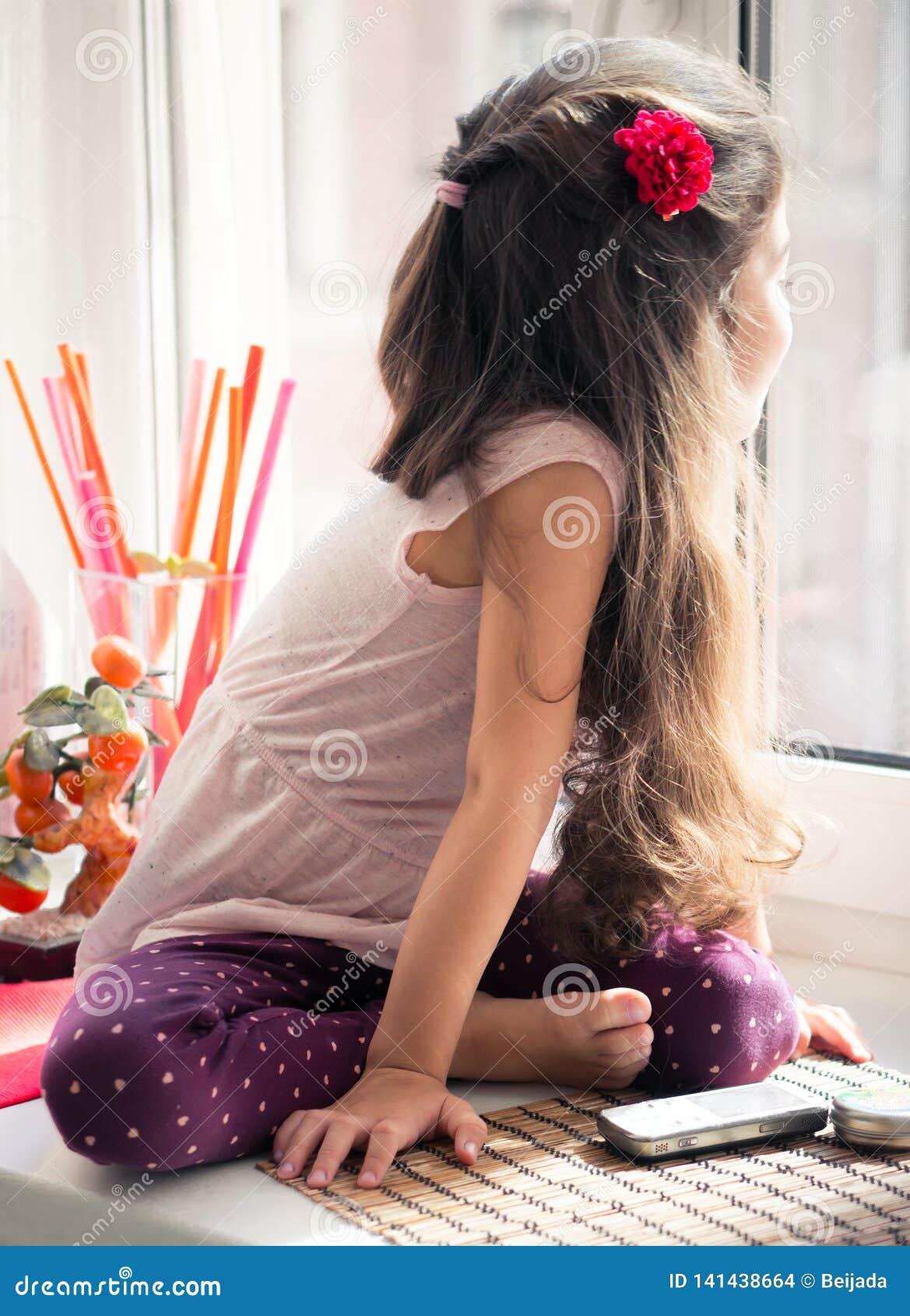 Μικρό κορίτσι στην παράθυρο-στρωματοειδή φλέβα που φαίνεται έξω το παράθυρο