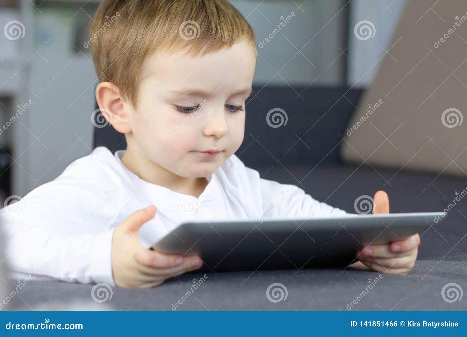 Μικρό παιδί που χρησιμοποιεί την ταμπλέτα οθονών επαφής στο σπίτι Ευτυχή έξυπνα σεμινάρια προσοχής παιδιών ή παίζοντας παιχνίδι σ