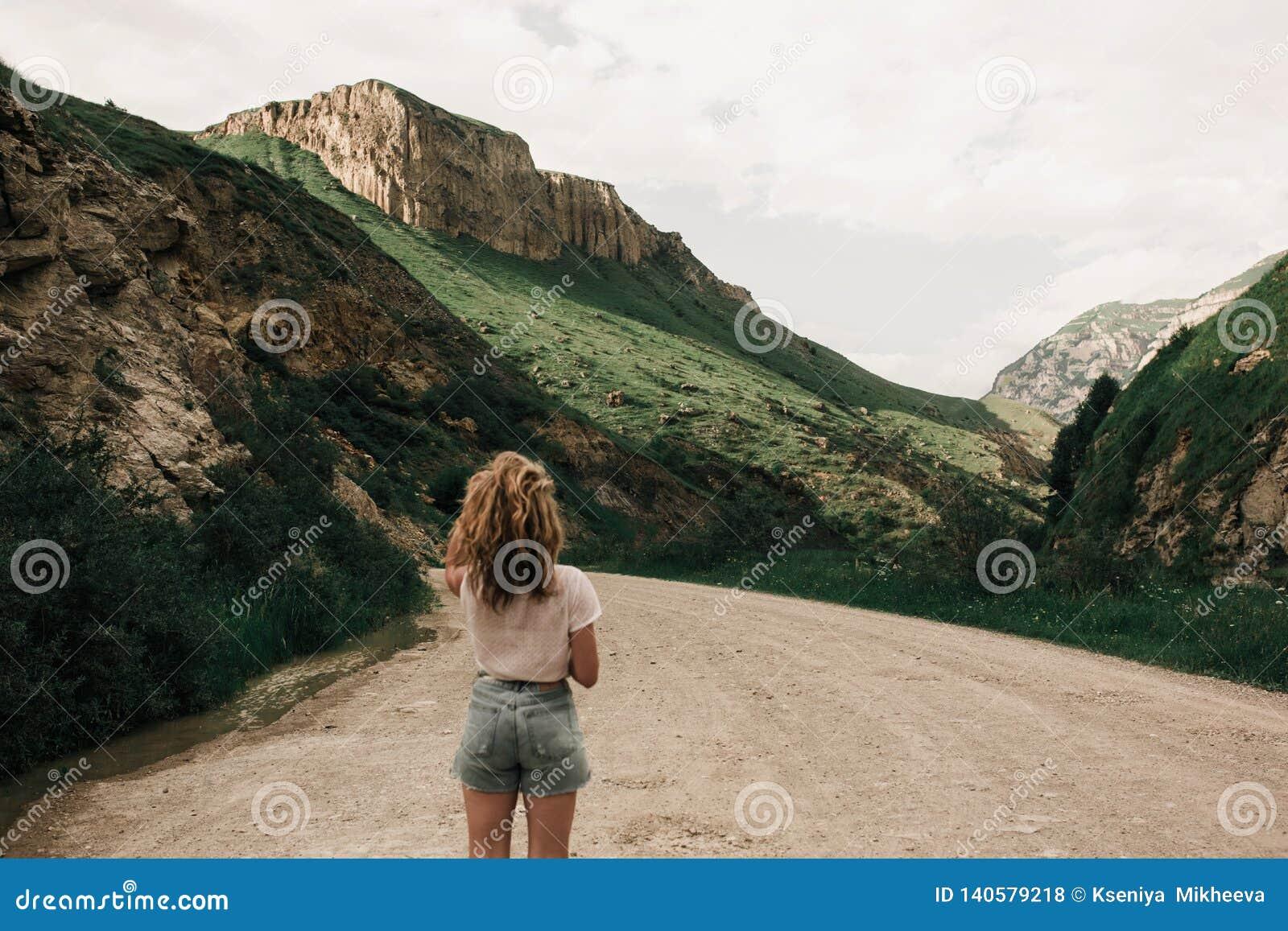 Μοντέρνο κορίτσι στα άσπρα ενδύματα που στέκονται στο δρόμο στις ορεινές περιοχές Πράσινα χλόη και βουνά