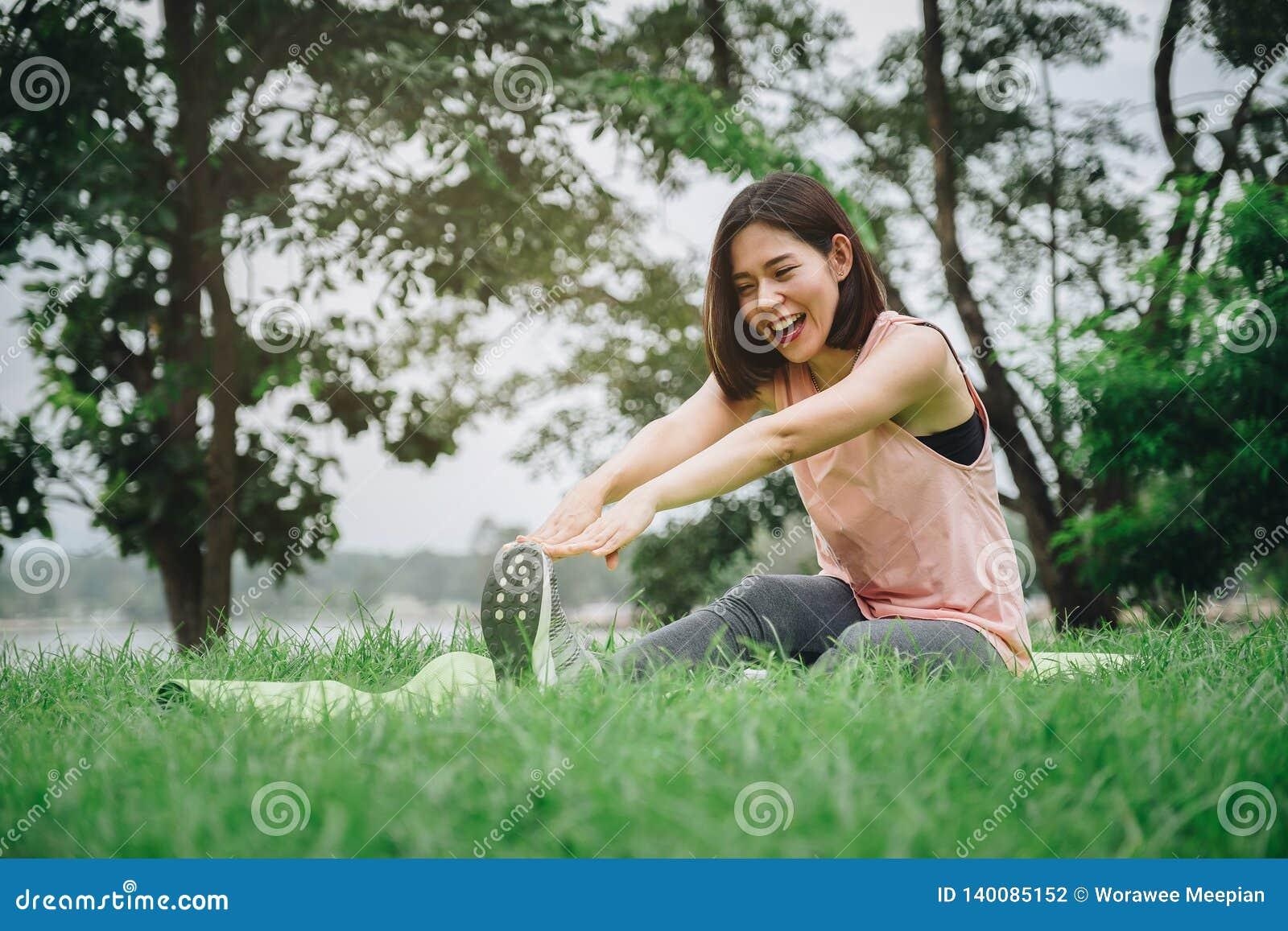 Νέα άσκηση χαμόγελου γυναικών στο πάρκο υγιής τρόπος ζωής έννοιας