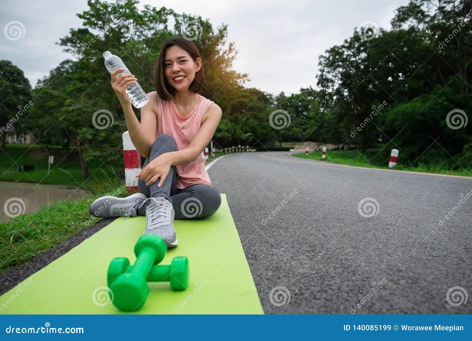 Νέα γυναίκα ικανότητας που χαμογελά και που κρατά το πόσιμο νερό μετά από τη γιόγκα στο πάρκο υγιής τρόπος ζωής έννοιας