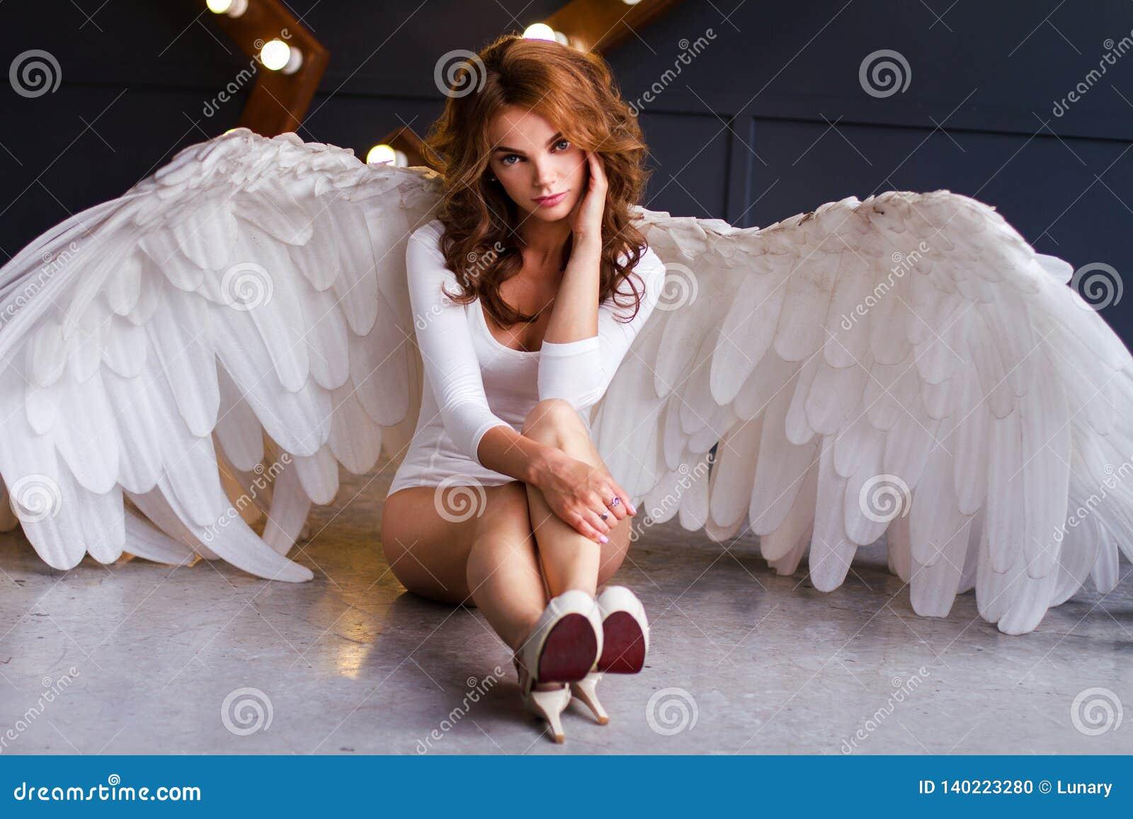 Νέα γυναίκα στο άσπρο κομπινεζόν με τα φτερά αγγέλου