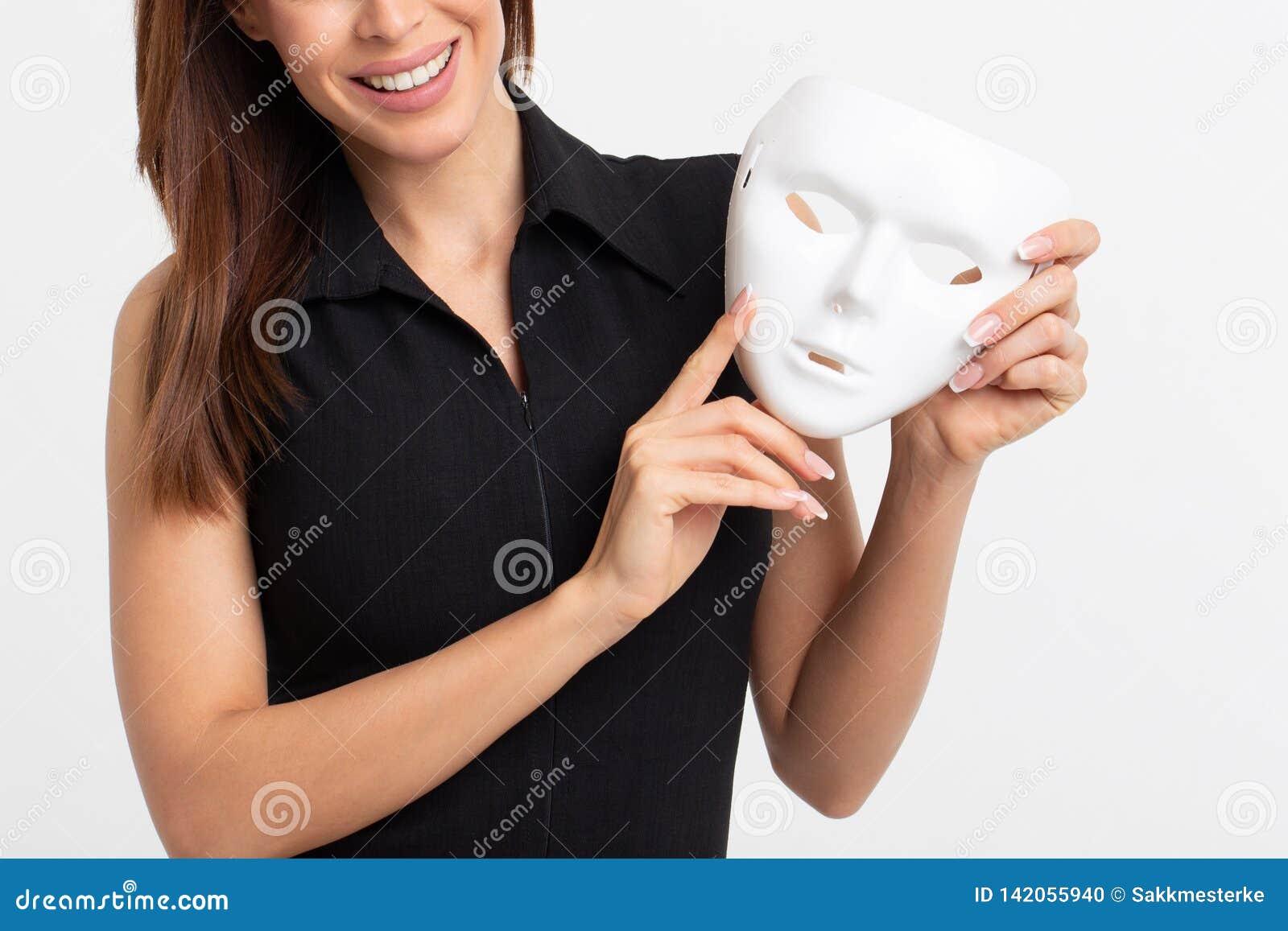 Νέα γυναίκα που κρατά την άσπρη μάσκα στο άσπρο υπόβαθρο