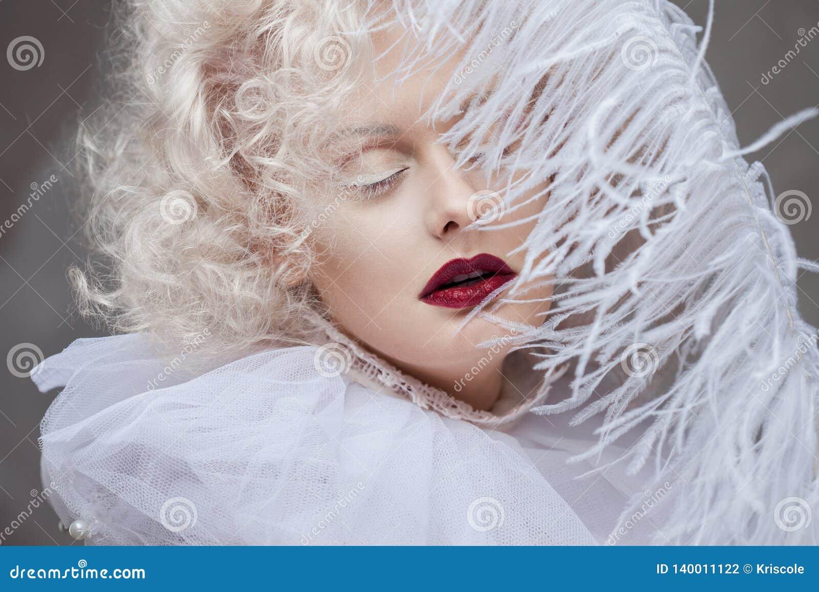 Νέα ελκυστική γυναίκα με το ξανθό και πορφυρό κραγιόν λευκόχρυσου