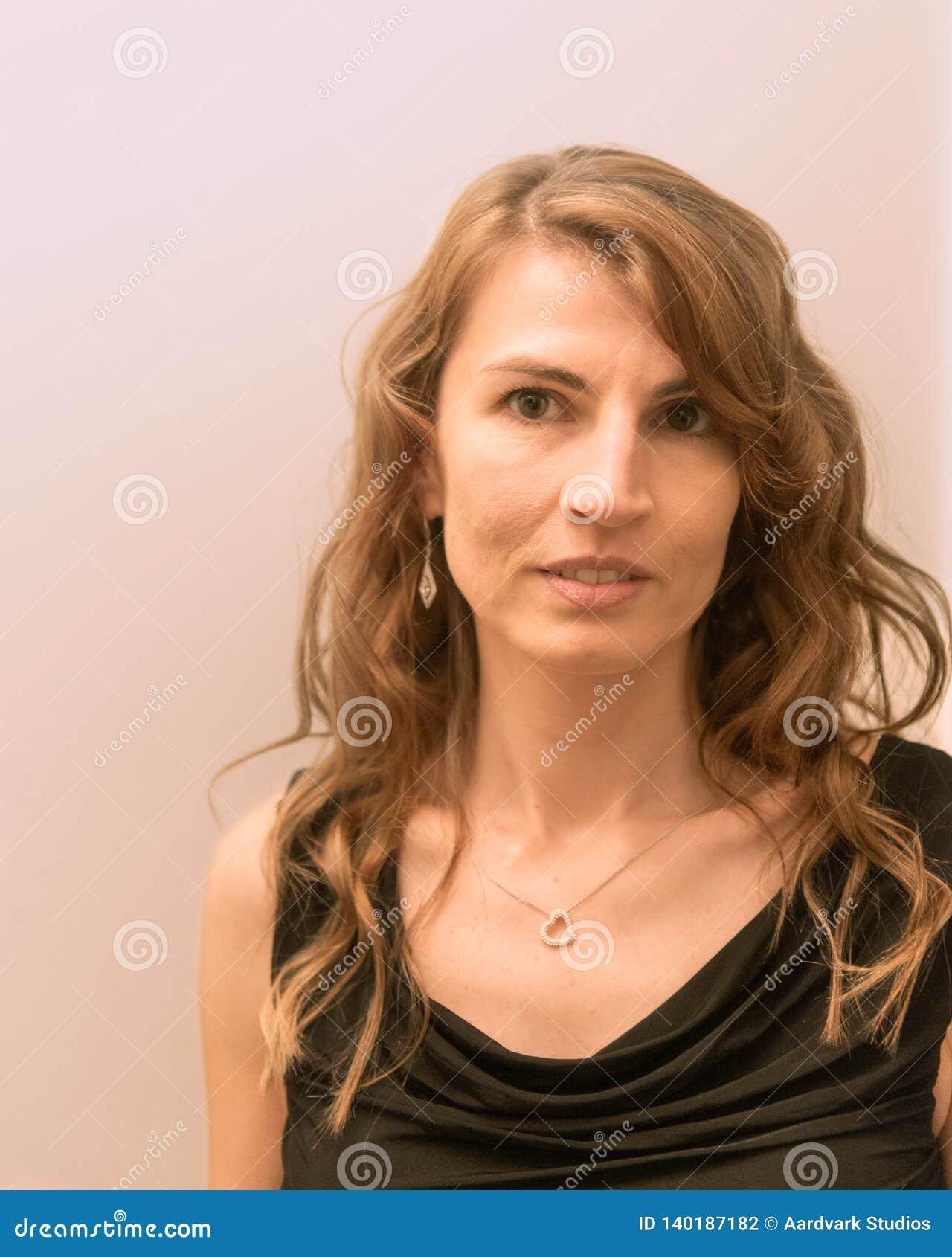 Νέα μέση ηλικίας λευκή γυναίκα με το hairstyle που χαμογελά φορώντας το μαύρο φόρεμα