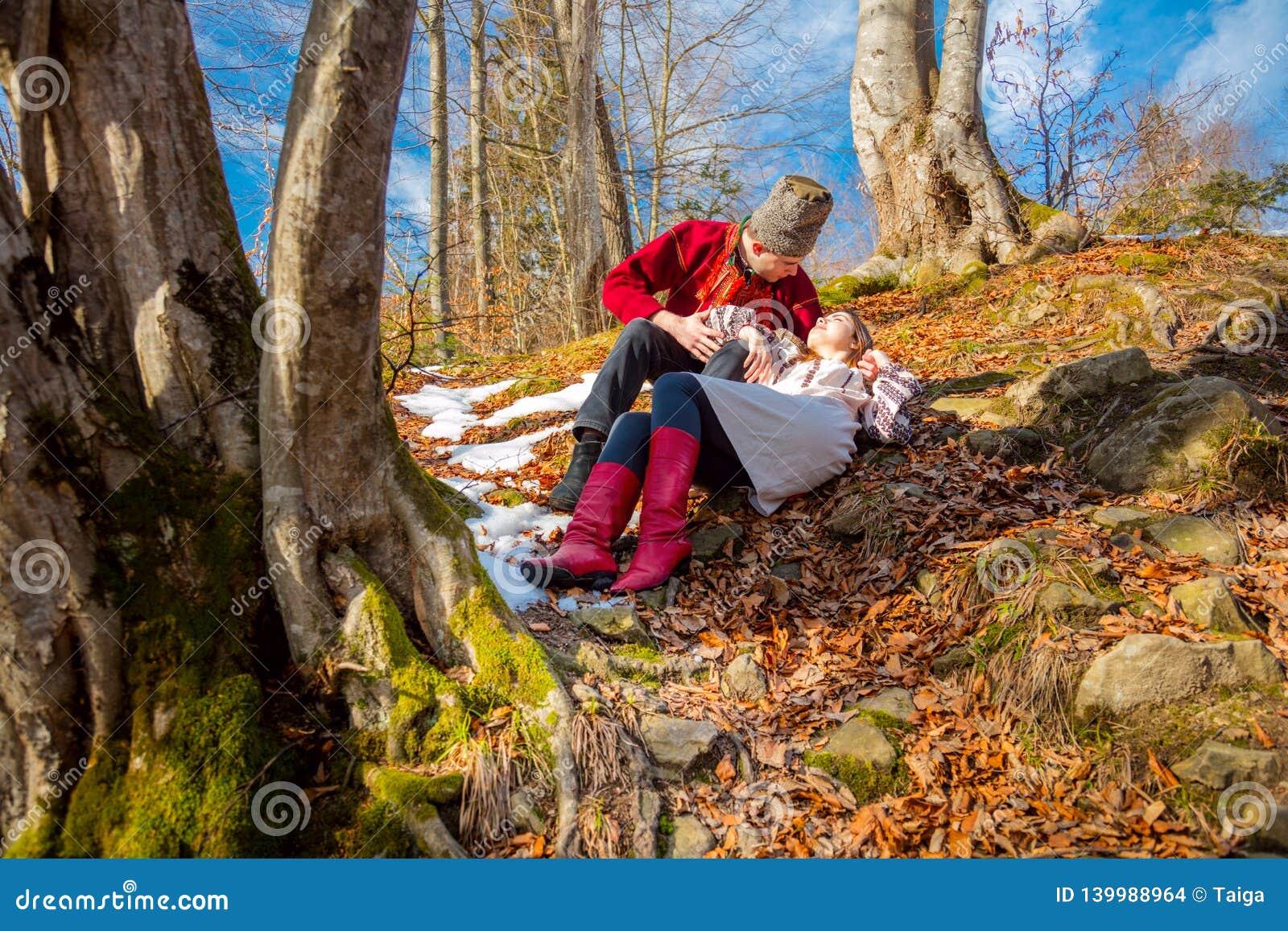 Νέο ζεύγος με τα παραδοσιακά ενδύματα στο φυσικό δάσος - αγάπη και ήλιος