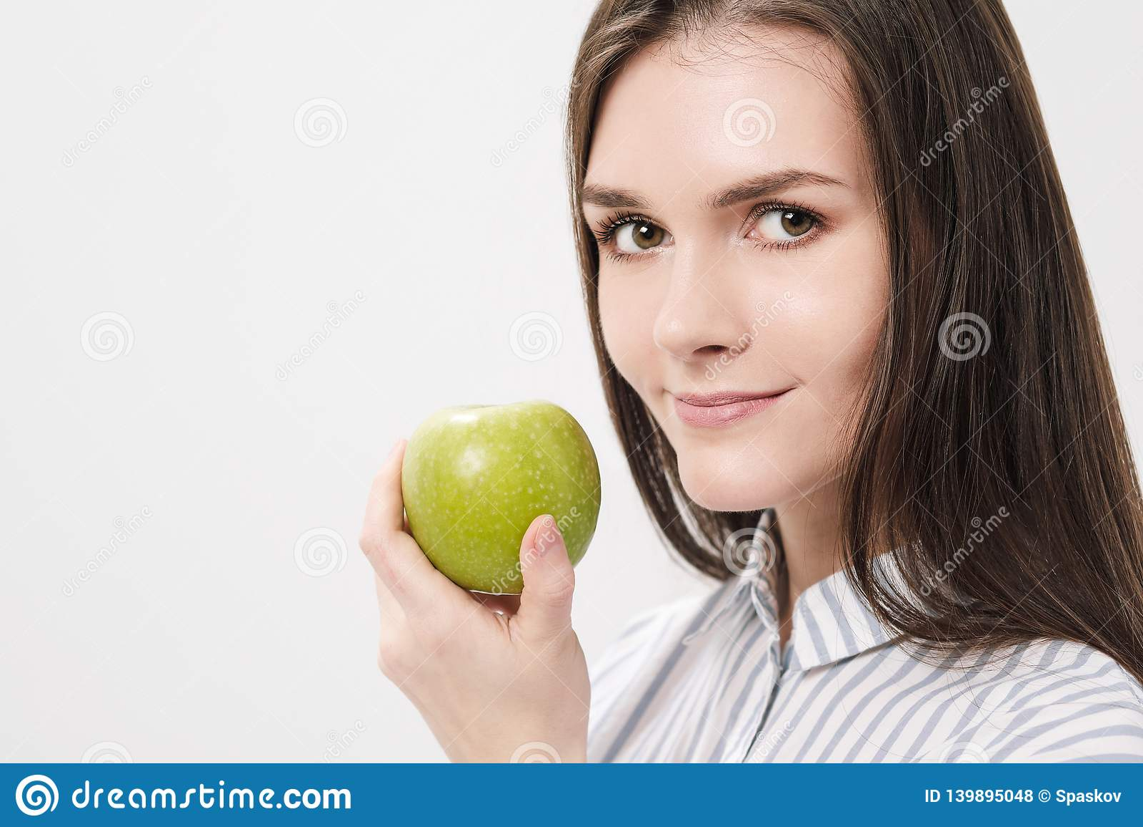 Νέο όμορφο κορίτσι brunette σε ένα άσπρο υπόβαθρο που κρατά ένα φρέσκο πράσινο μήλο