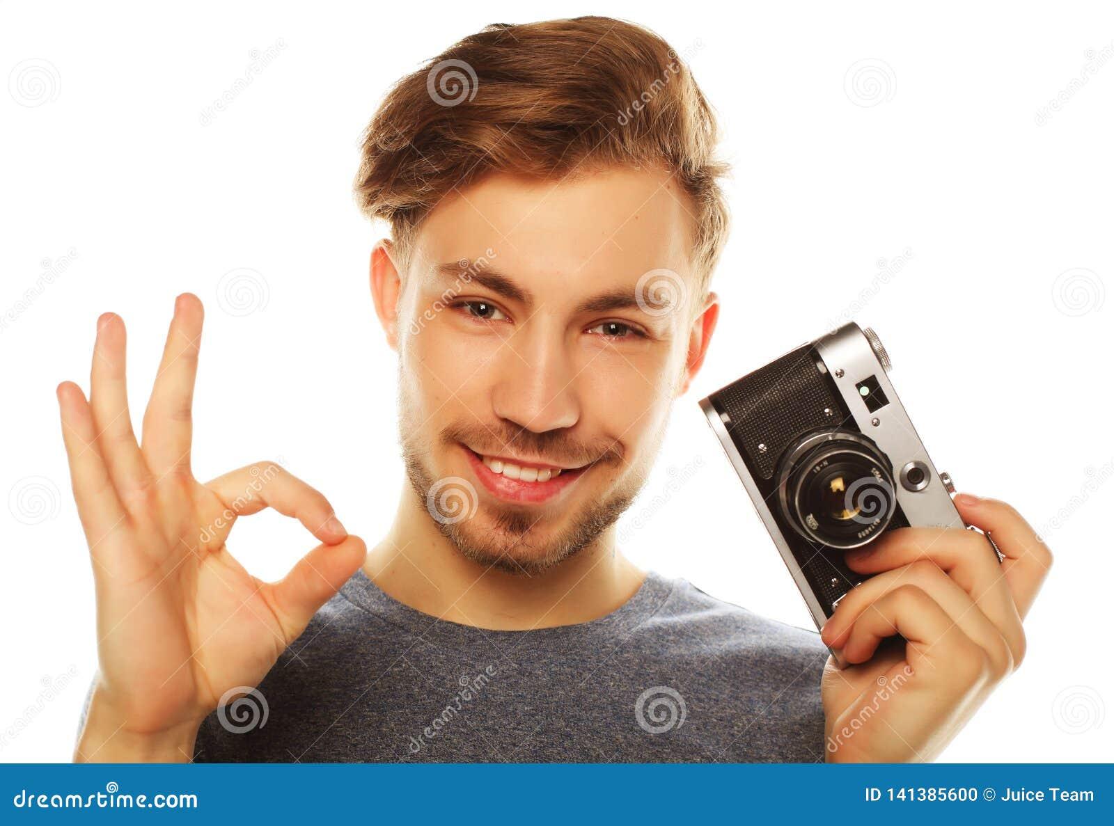 Νεαρός άνδρας με τη φωτογραφική μηχανή Απομονωμένος πέρα από την άσπρη ανασκόπηση