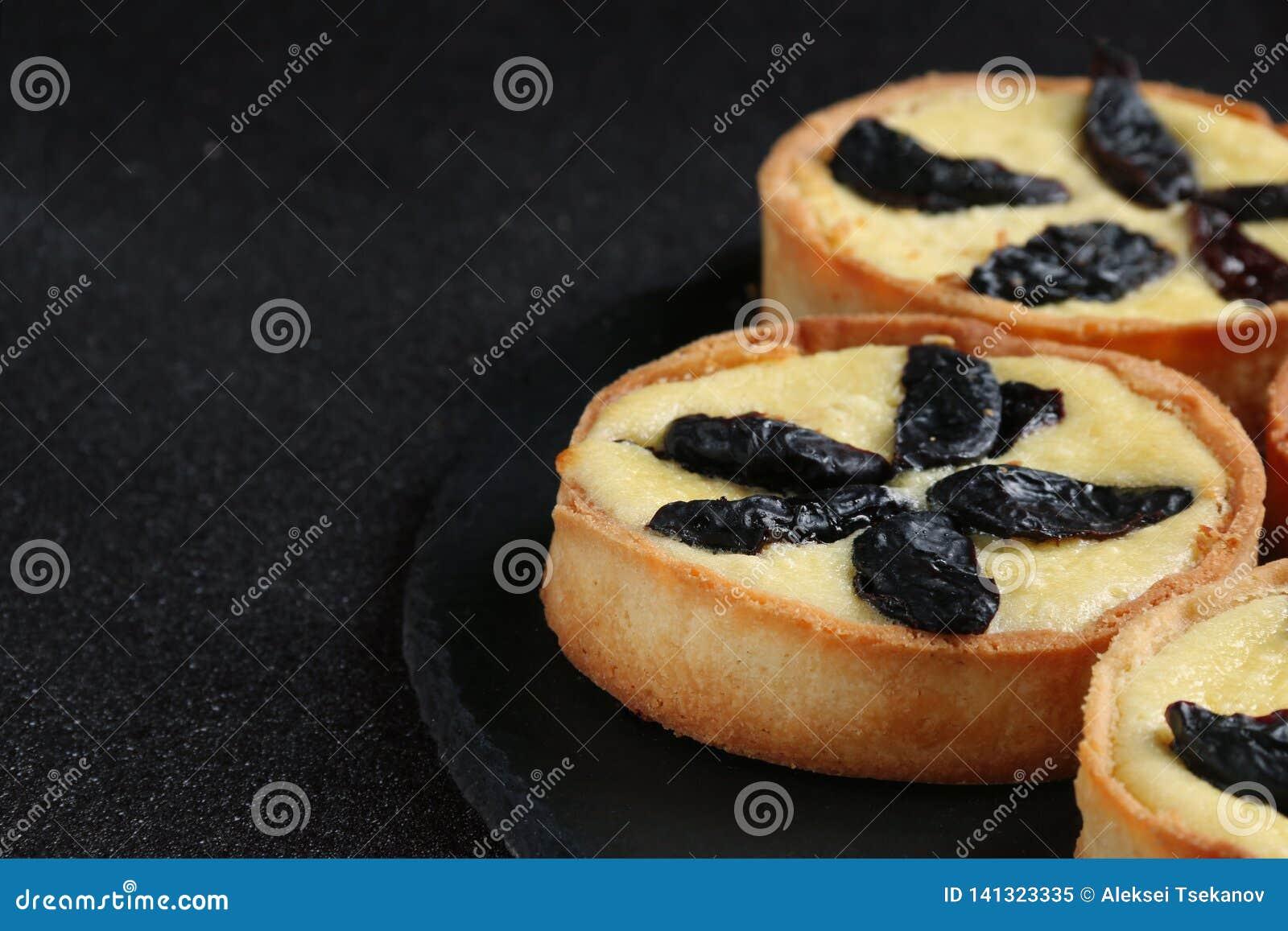 Ξινός με ξινό στενό επάνω κρέμας στο σκοτεινό υπόβαθρο cheesecake στο πιάτο πλακών