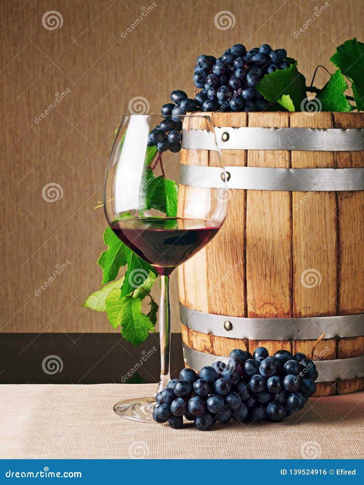 Ξύλινα βαρέλι κρασιού και ποτήρι του κόκκινου κρασιού στον πίνακα