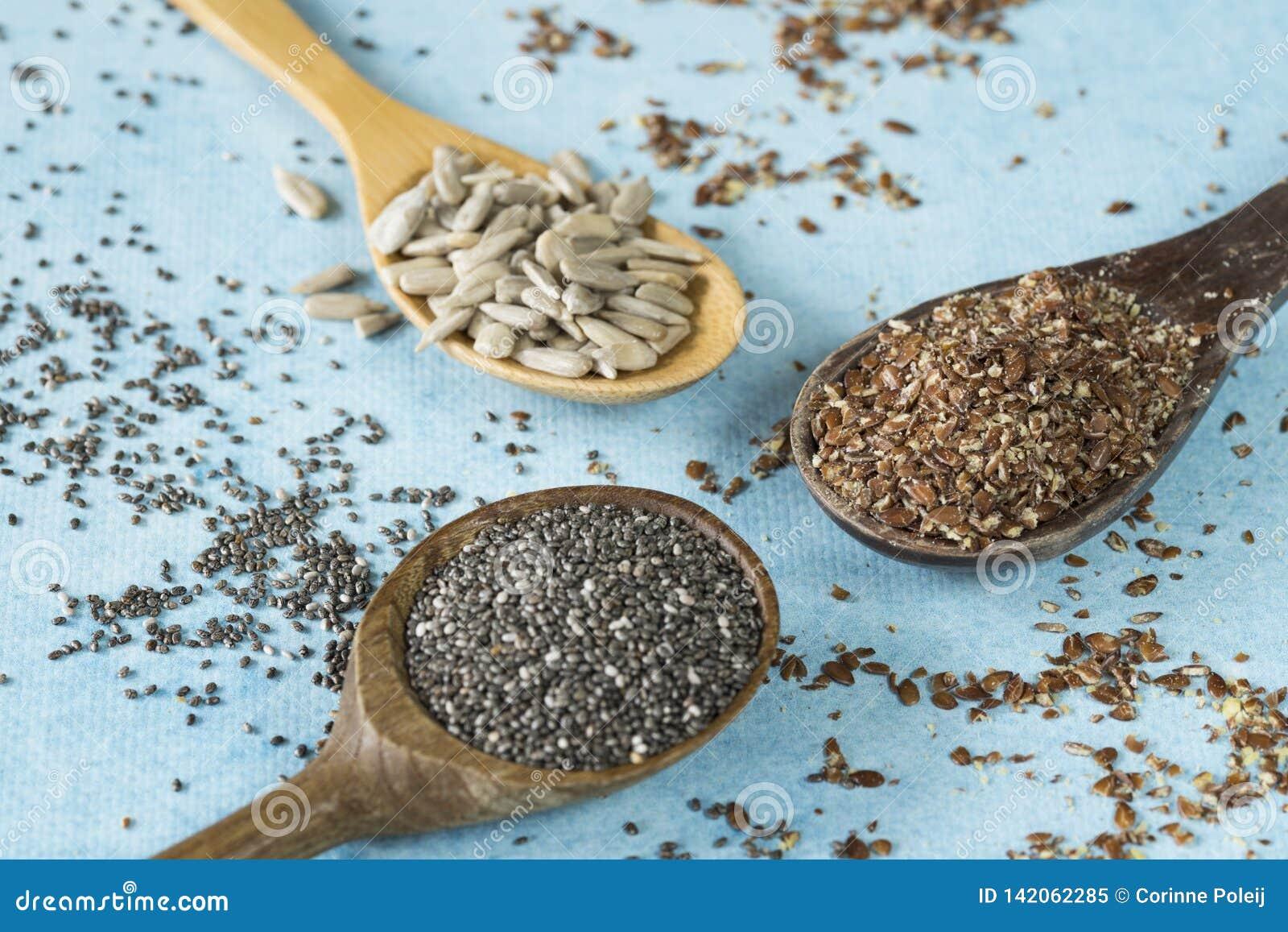 Ξύλινα κουτάλια με τους σπόρους ηλίανθων, το chia και το λιναρόσπορο