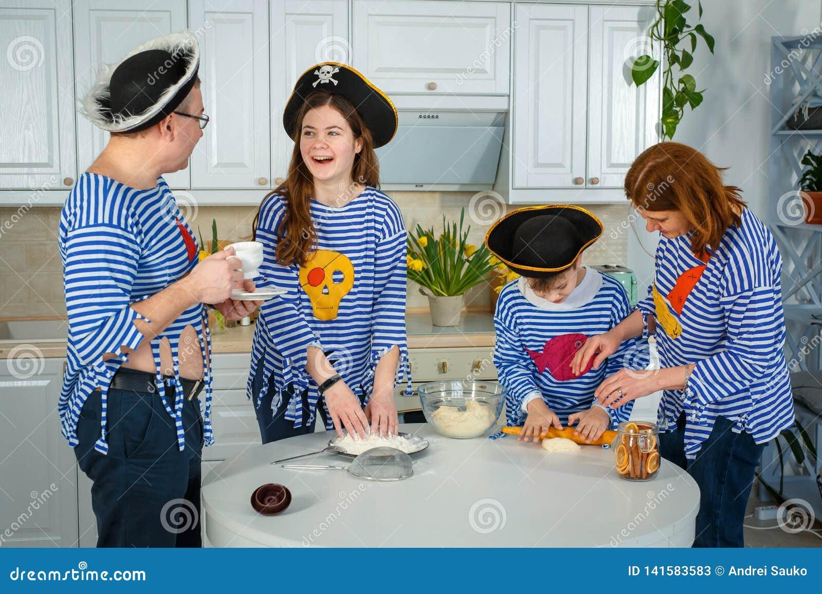 Οι οικογενειακοί μάγειρες από κοινού Σύζυγος, σύζυγος και τα παιδιά τους στην κουζίνα Η οικογένεια ζυμώνει τη ζύμη με το αλεύρι