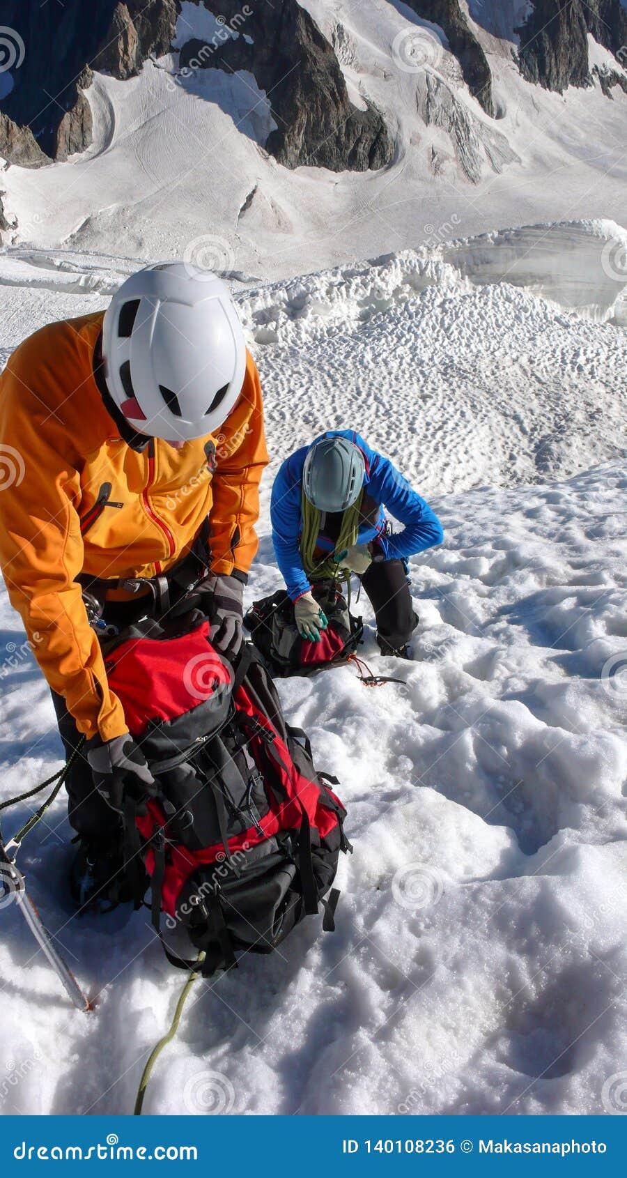 Οι ορειβάτες βουνών παίρνουν ένα σπάσιμο υψηλό επάνω σε έναν παγετώνα στις γαλλικές Άλπεις