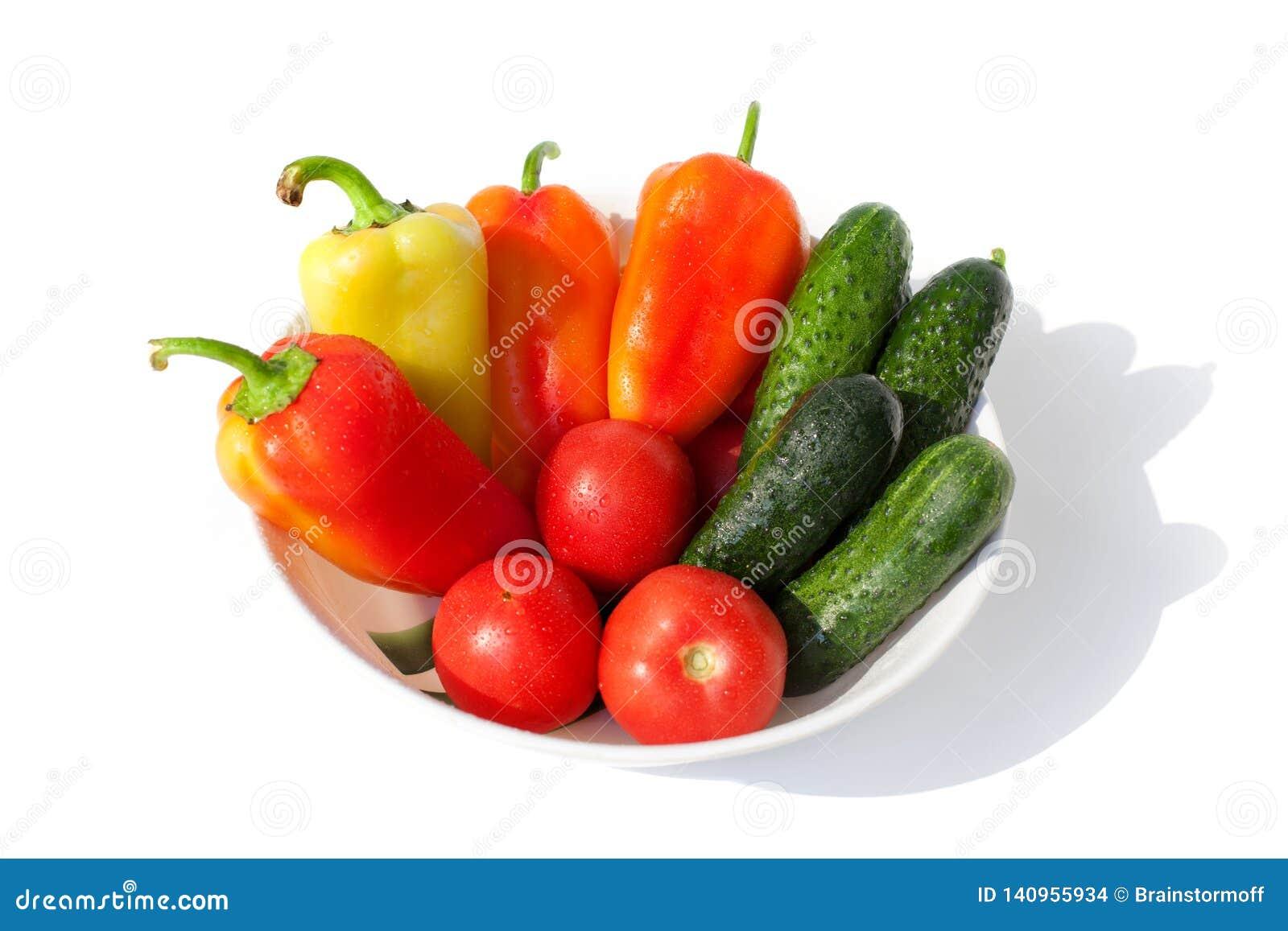 Ολόκληρα αγγούρια λαχανικών, πιπέρια κουδουνιών και κόκκινο πράσινο κίτρινο πορτοκάλι ντοματών στις πτώσεις νερού στην άσπρη απομ