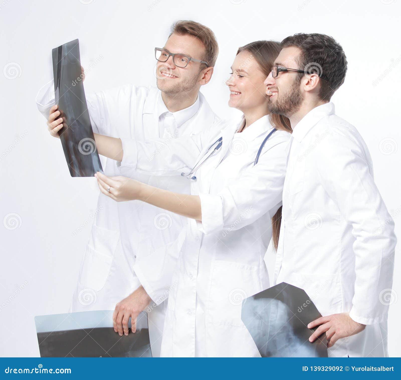 Ομάδα χαμογελώντας γιατρών που συζητούν τις ακτίνες X Απομονωμένος στο λευκό