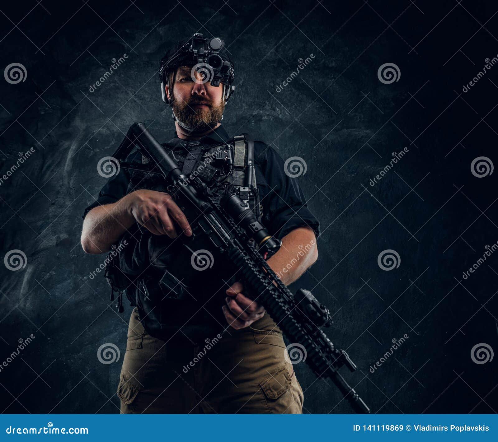 Ο γενειοφόρος στρατιώτης ειδικών δυνάμεων ή ο ιδιωτικός στρατιωτικός ανάδοχος που κρατά ένα επιθετικό τουφέκι και παρατηρεί τα πε