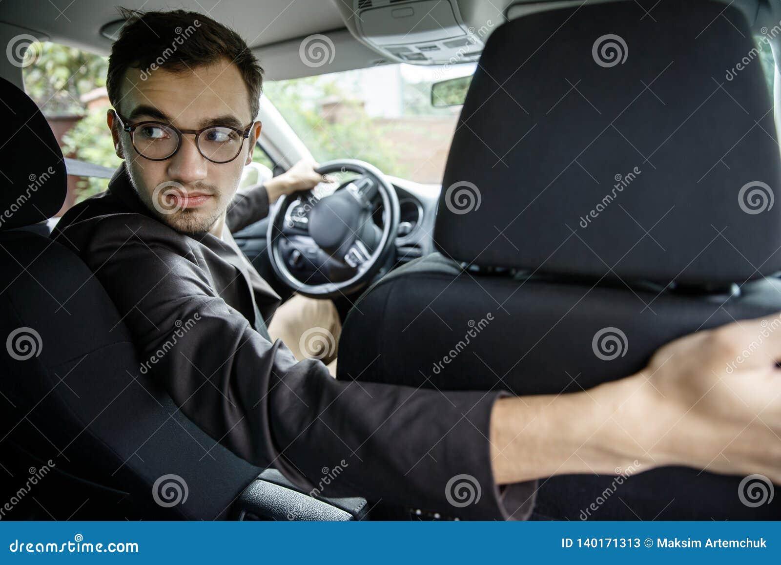 Ο νέος ταξιτζής ξανακοιτάζει πέρα από τα καθίσματα Κάθεται στο αυτοκίνητό του